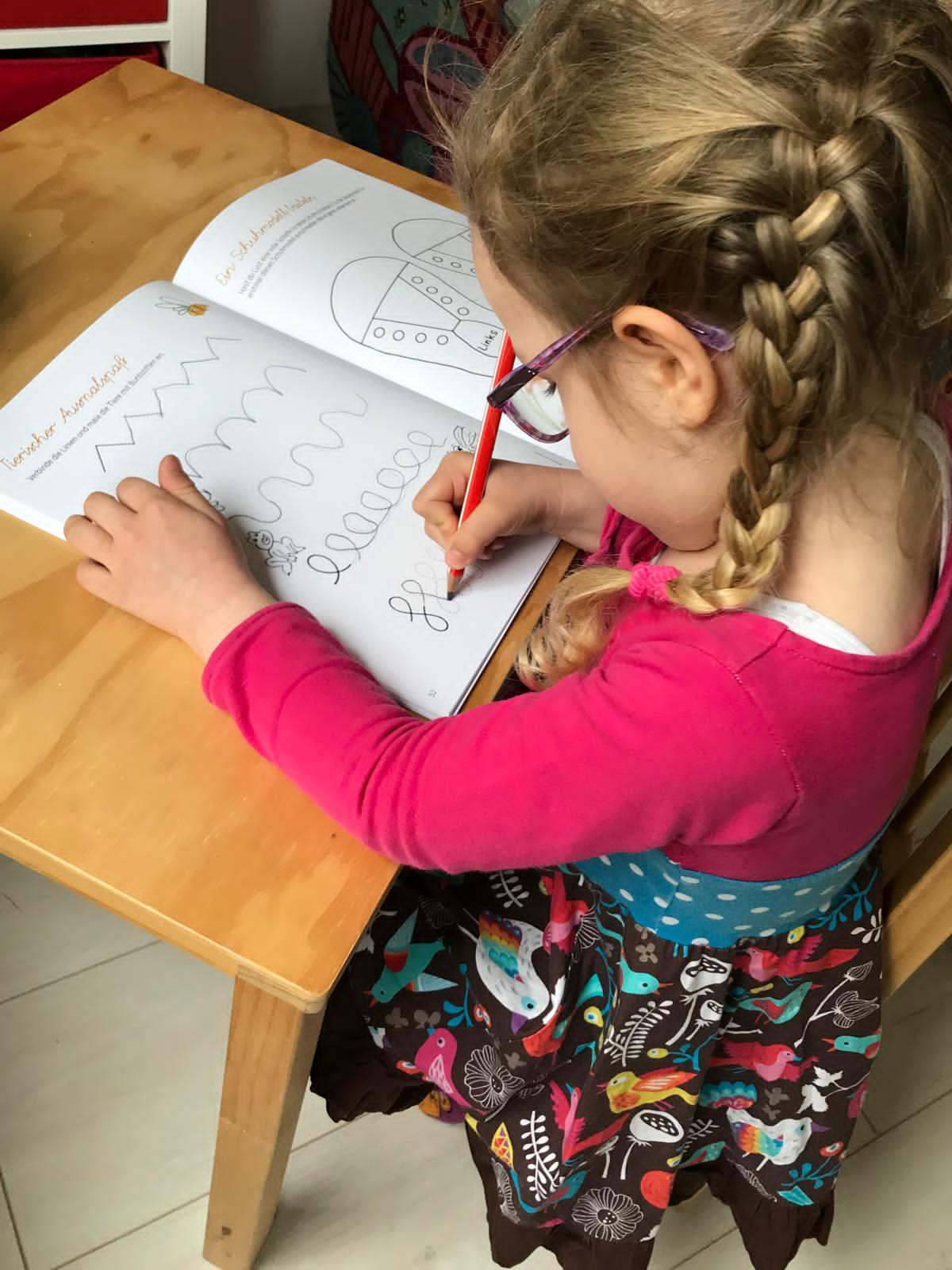 Ein Mädchen, an einem Kinderschreibtisch sitzend, malt in einem Ausmalbuch