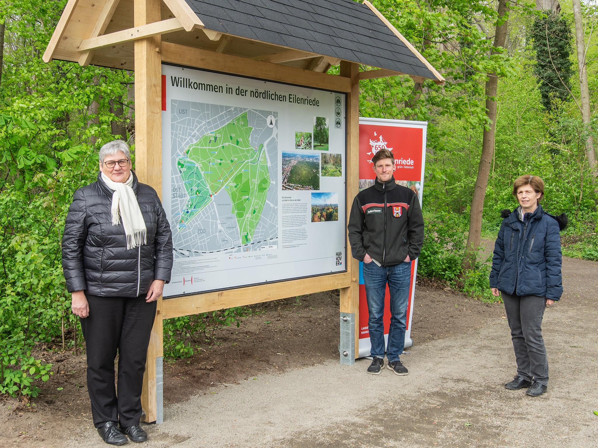 Drei Personen stehen an einem Waldeingangsschild