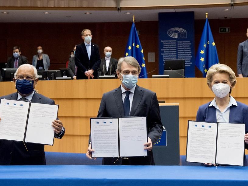 Drei Personen halten in einem Sitzungssaal Mappen mit Dokumenten in die Höhe