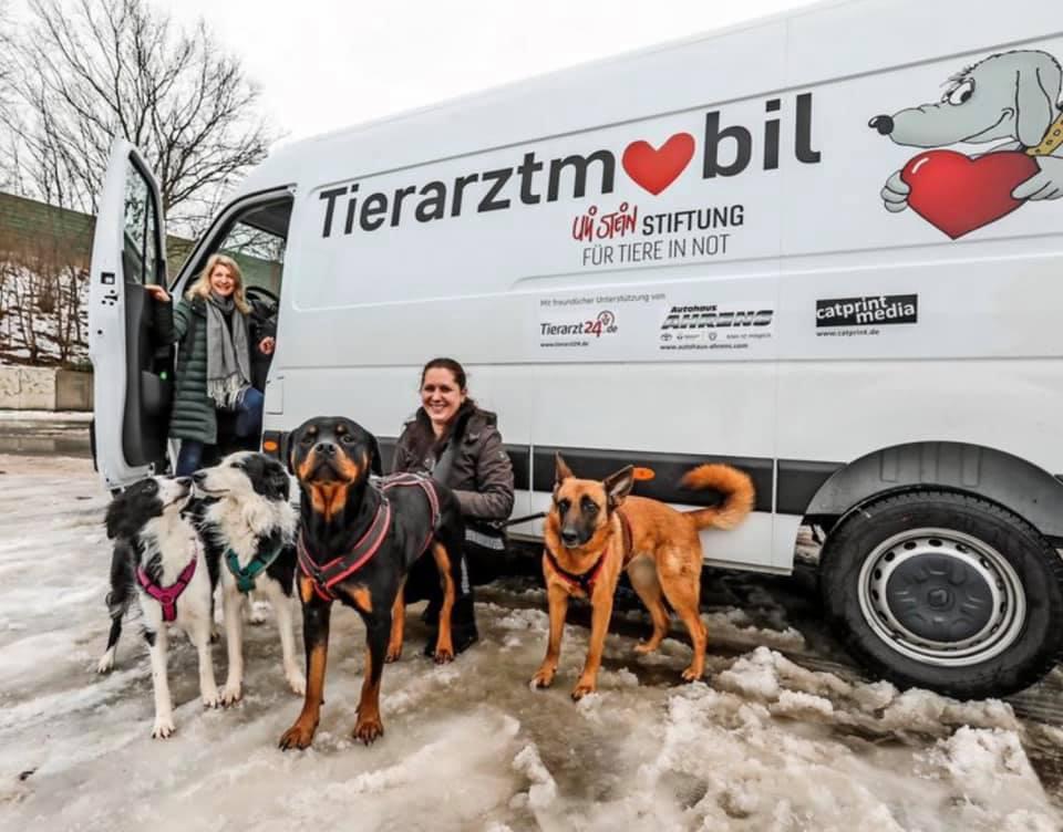 Zwei Frauen mit Hunden vor einem Transporter. Darauf steht Tierarztmobil.
