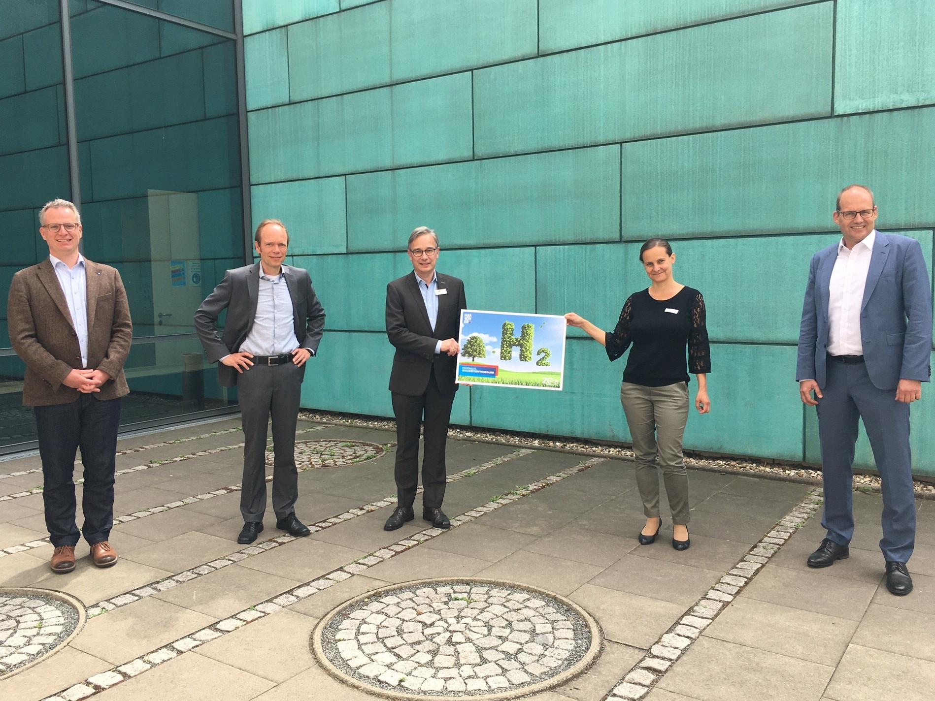 """Fünf Personen stehen vor einem Gebäude, zwei davon halten gemeinsam ein Plakat auf dem """"H2"""" steht."""