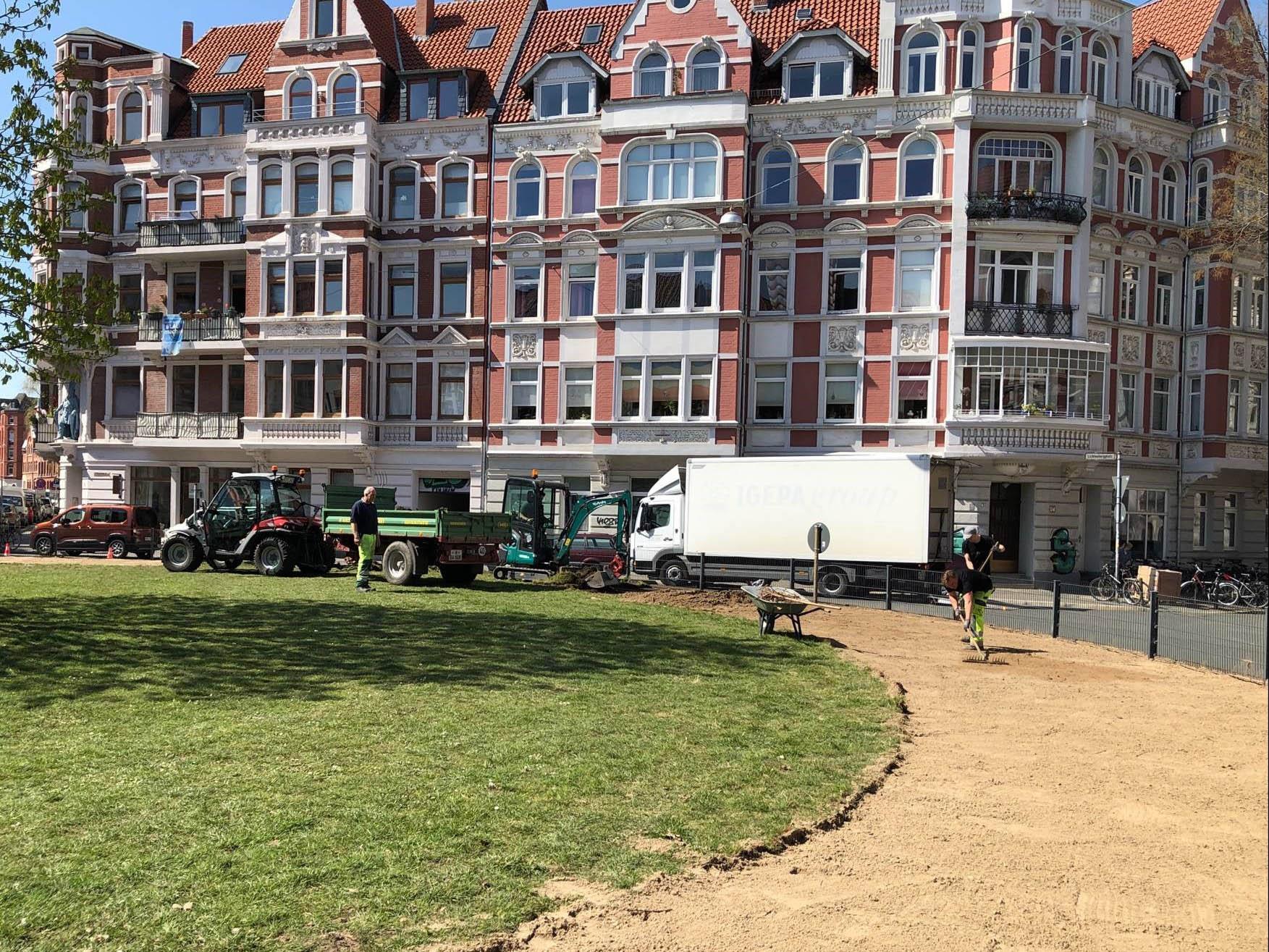 Ein grüner Platz, auf dem Arbeiten durchgeführt werden. Im Hintergrund Wohnhäuser.