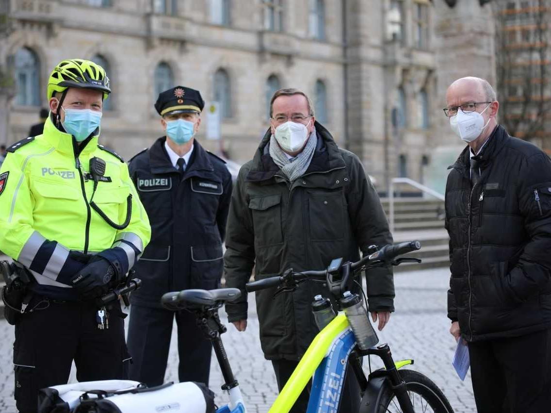 Zwei Männer in Polizeiuniformen und zwei Männer in Anzügen stehen hinter einem Fahrrad.