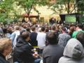 Viele Menschen in einem Biergarten vor einer Leinwand, auf der ein Fußballspiel gezeigt wird.