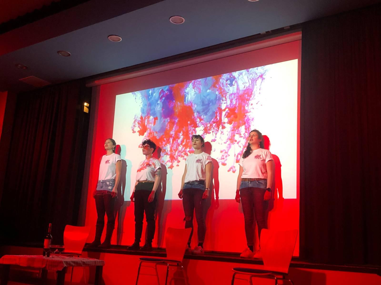 Vier Frauen stehen auf einer rot beleuchteten Bühne
