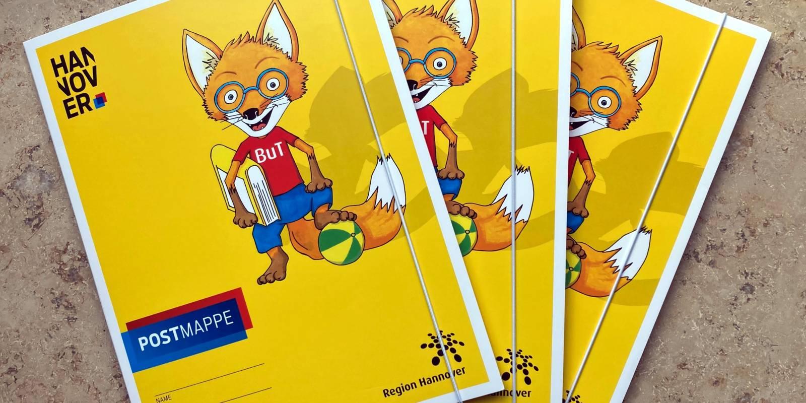 Gelbe Postmappen, bedruckt mit dem BuT-Fuchs, liegen gestapelt aufeinander.