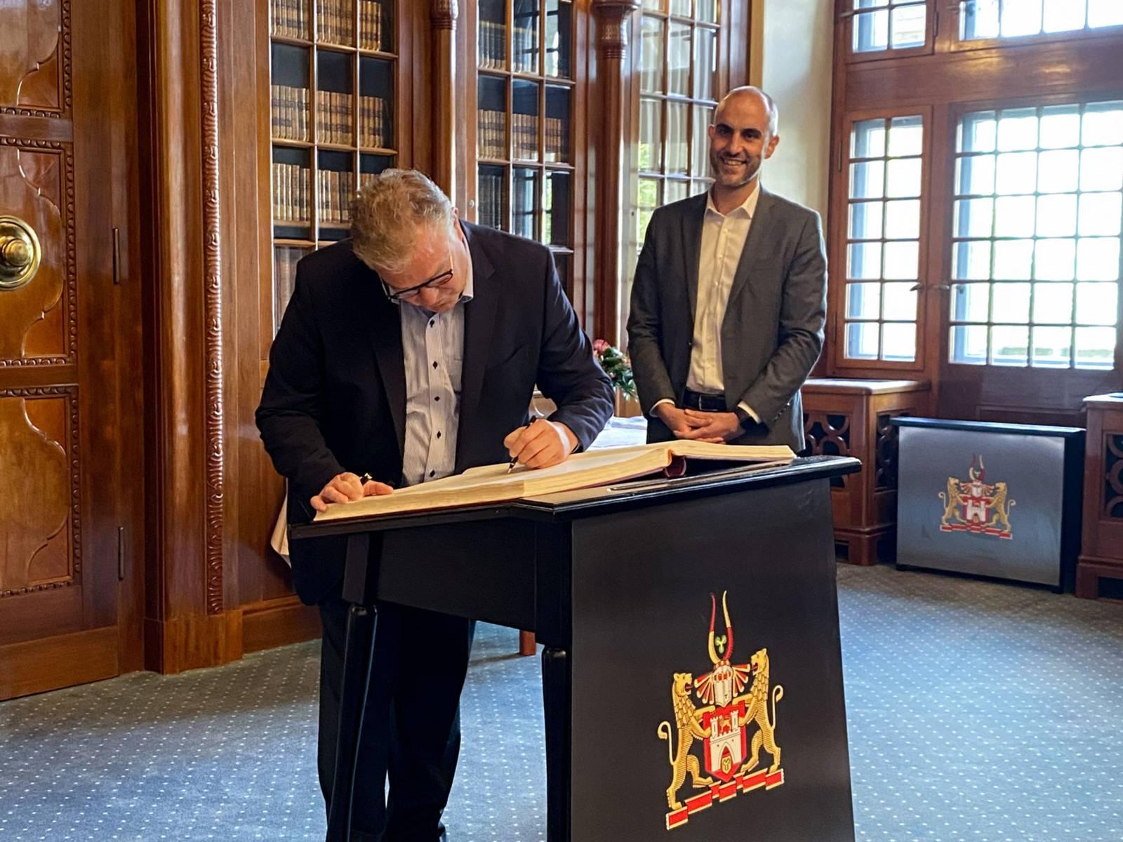 Zwei Männer stehen in einen Büro und einer trägt sich in das goldene Buch der Stadt ein.