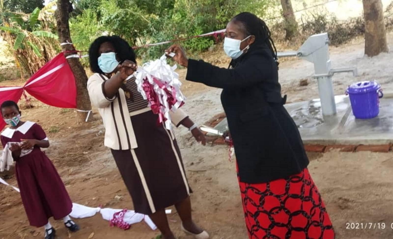 Zwei Frauen mit einer Papierschleife in den Händen auf dem geschmückten Schulgelände. Daneben steht eine Schülerin. Im Hintergrund der neu gebaute Brunnen.