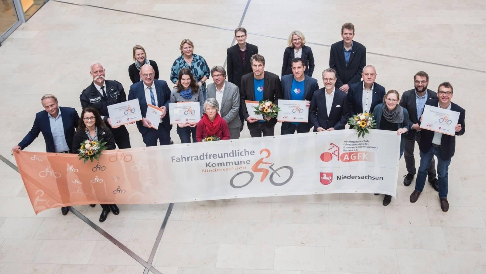 """Zwölf Männer und 7 Frauen stehen gemeinsam hinter einem Banner. Auf dem Banner steht """"Fahrradfreundliche Kommune Niedersachsen""""."""