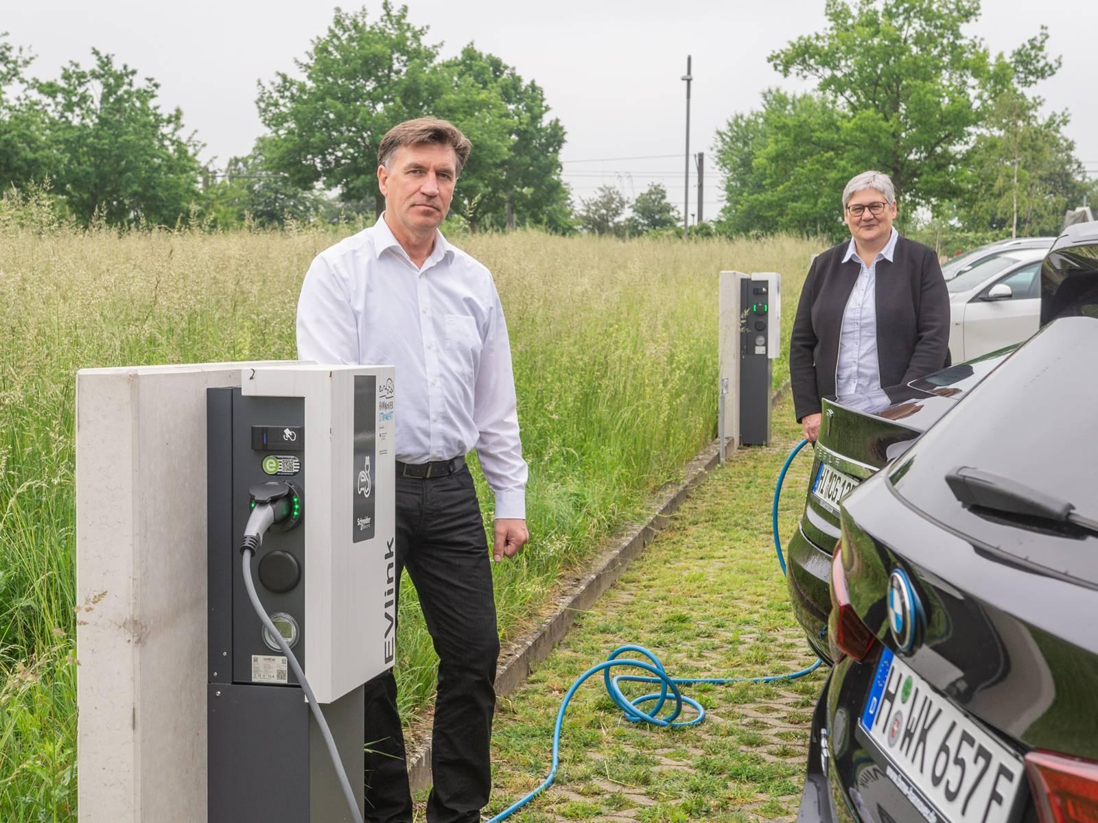 Ein Mann und eine Frau stehen an Ladesäulen für Elektroautos, die gerade angeschlossen sind