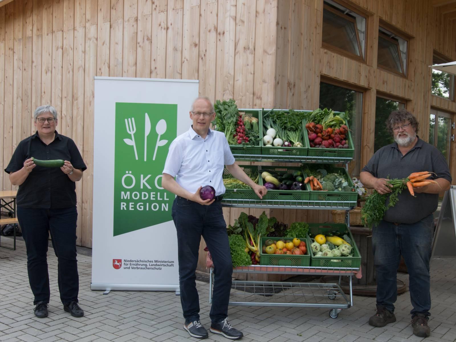 Drei Personen, die Gemüse in den Händen halten, stehen vor einem Schild der Ökomodellregion und einem Gemüsestand