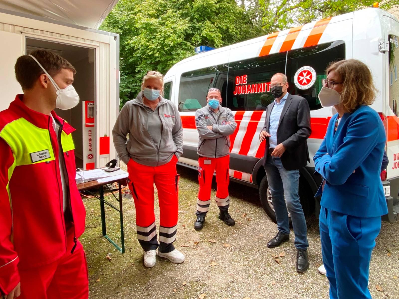 Drei Johanniter und ein Mann sowie ein Frau stehen vor einem Krankentransportfahrzeug.