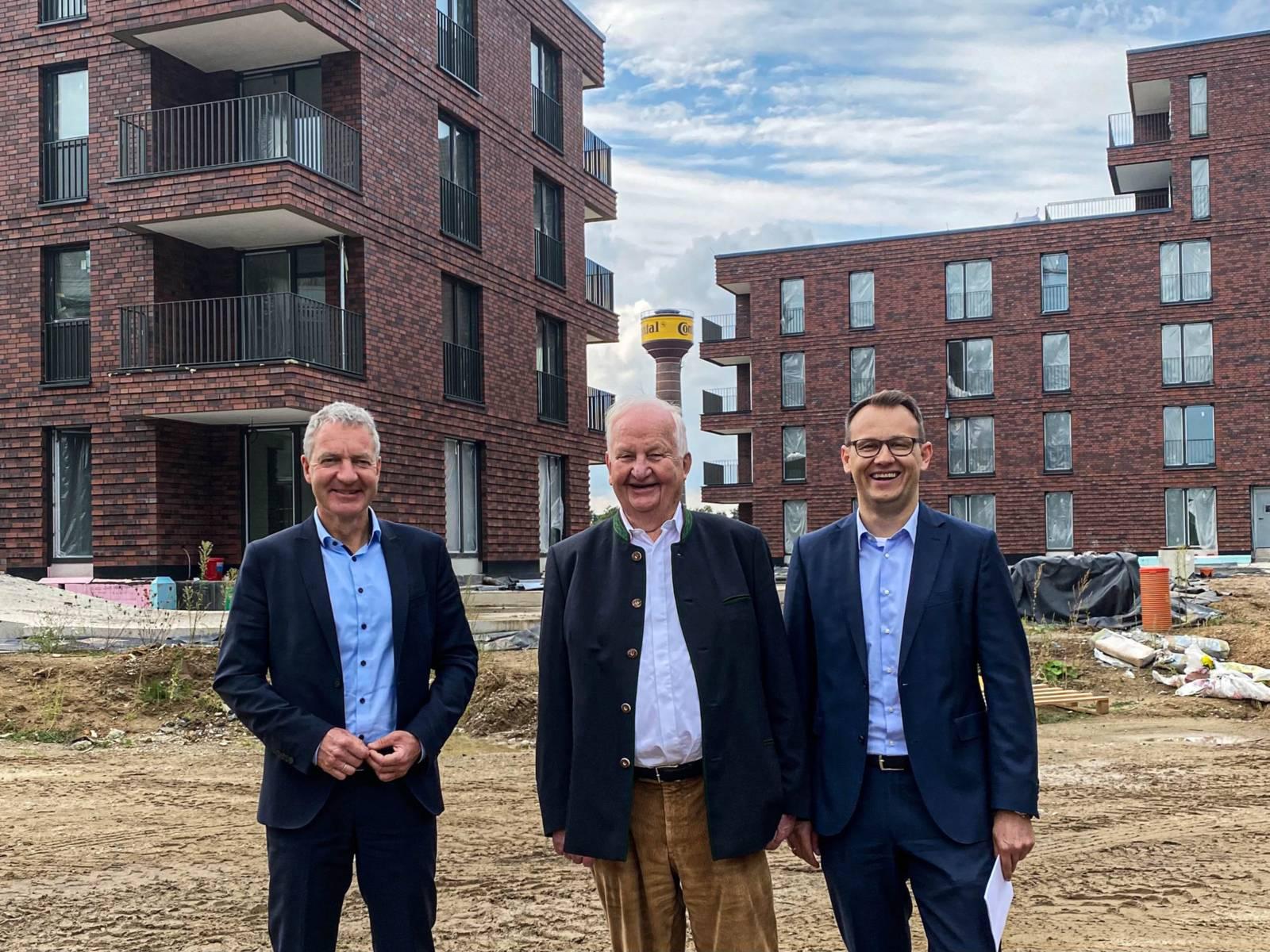 Drei Männer zwischen Gebäuden.