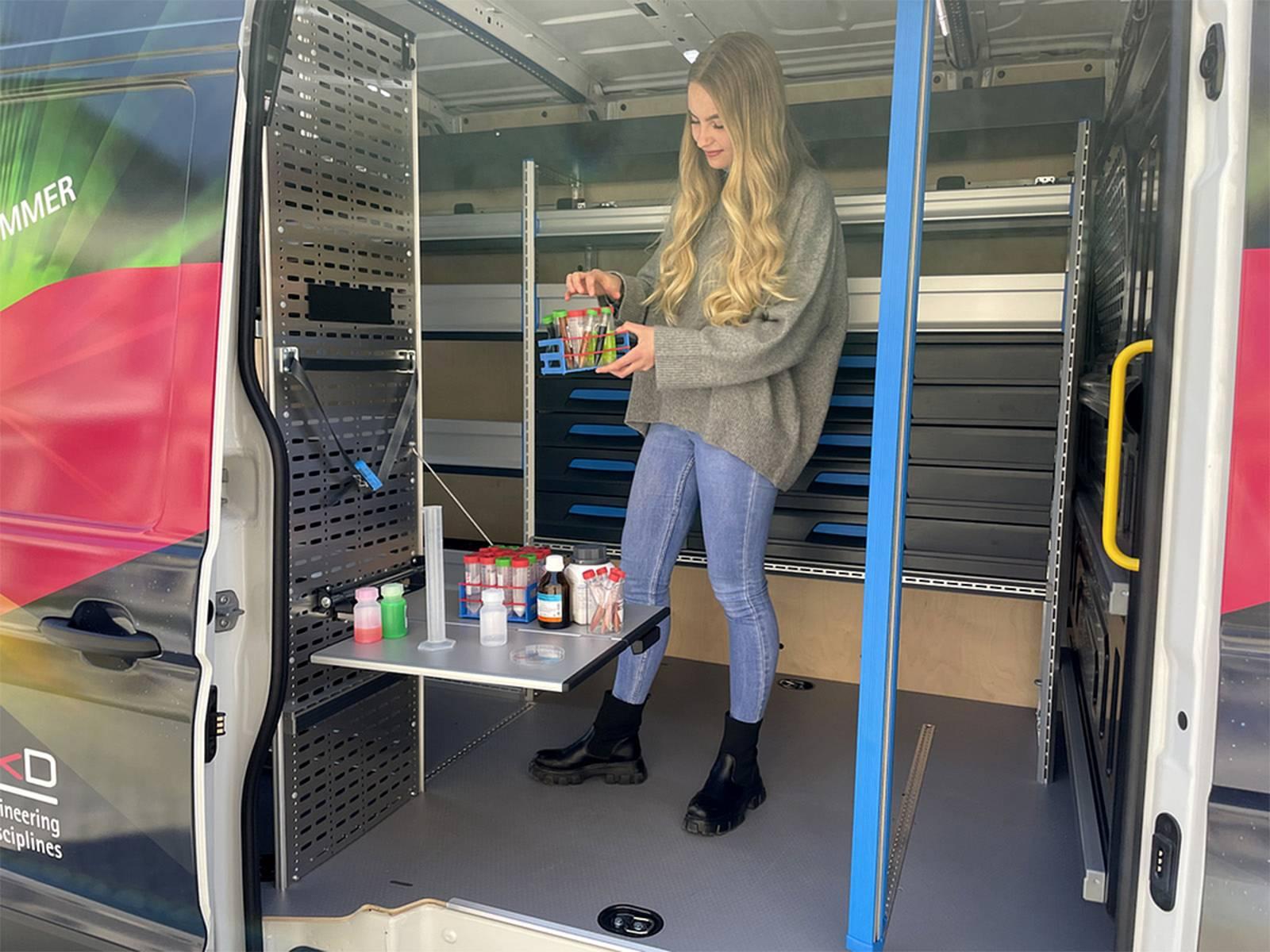 Junge Frau steht in einem Transporter, dessen Innenraum zu einem Labor umgebaut ist.