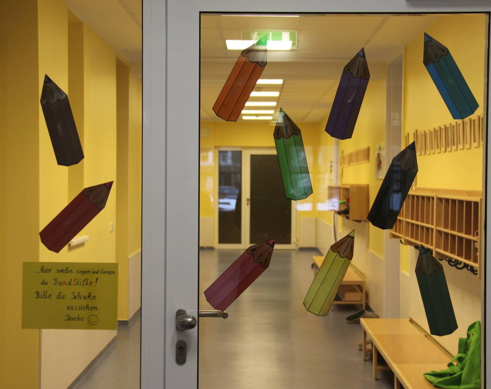 Das Foto zeigt eine Glastür mit grauem Metallrahmen. Das Glas der Tür ist mit mehreren Aufklebern in Form von verschiedenfarbigen Buntstiften beklebt. Hinter der Tür sieht man einen langen Flur, dessen Wände gelb gestrichen sind. An der rechten Wand sind einige Regale angebracht und es stehen niedrige Bänke direkt an der Wand.