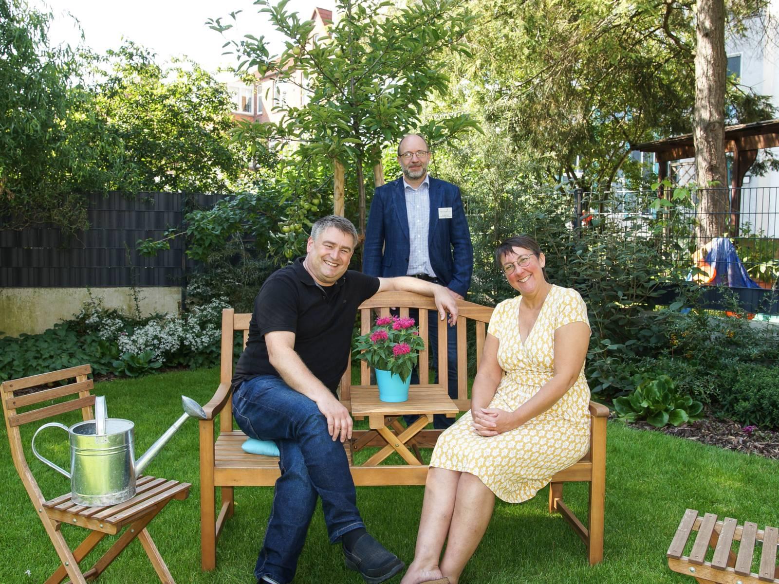 Drei lächelnde Personen in einem Garten.