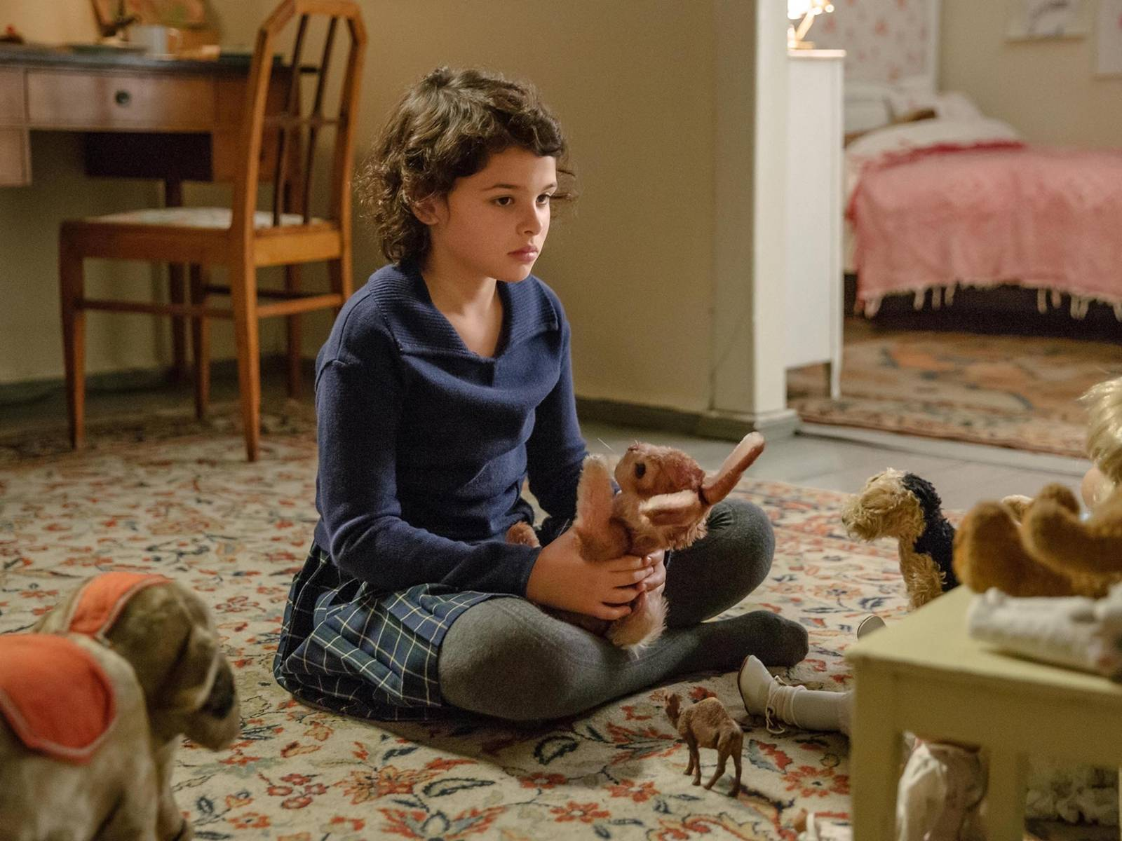Ein zirka 10jähriges Mädchen sitzt im Schneidersitz auf einem Teppich. In den Händen hält sich ein rosa Kaninchen. Traurig schaut sie auf weitere Stofftiere.