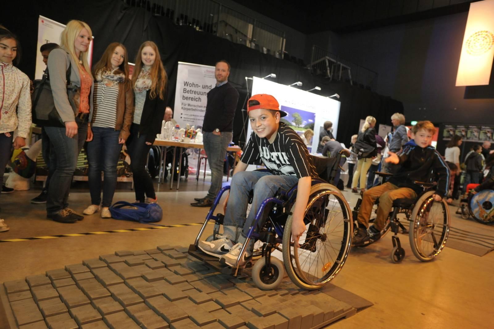 Ein Junge im Rollstuhl auf einem Hindernisparcours für Rollstühle