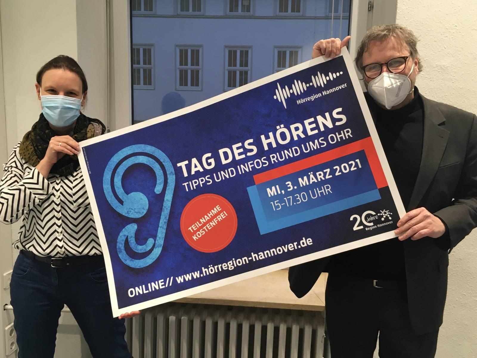 Zwei Menschen halten ein Plakat zum Tag des Hörens in die Höhe