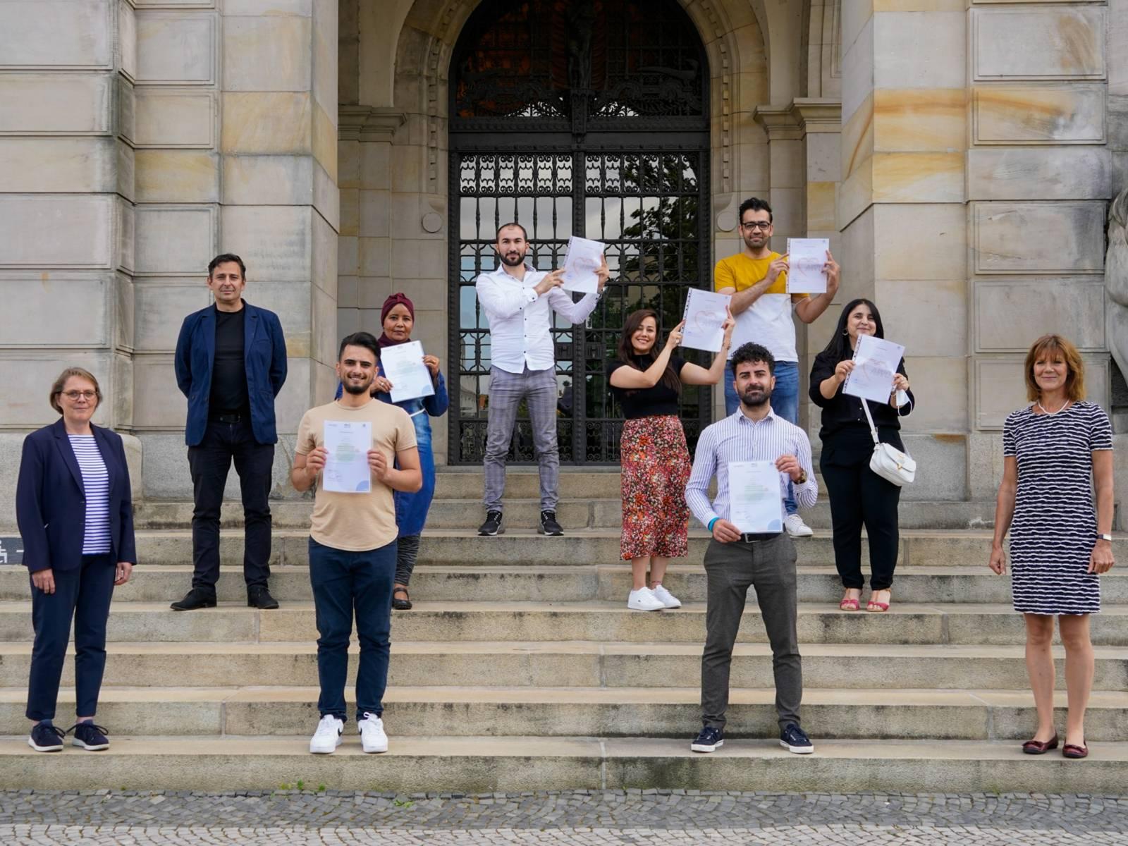 Zehn Personen stehen auf einer Treppe am Rathaus, einige halten ihr Zertifikat in die Höhe.