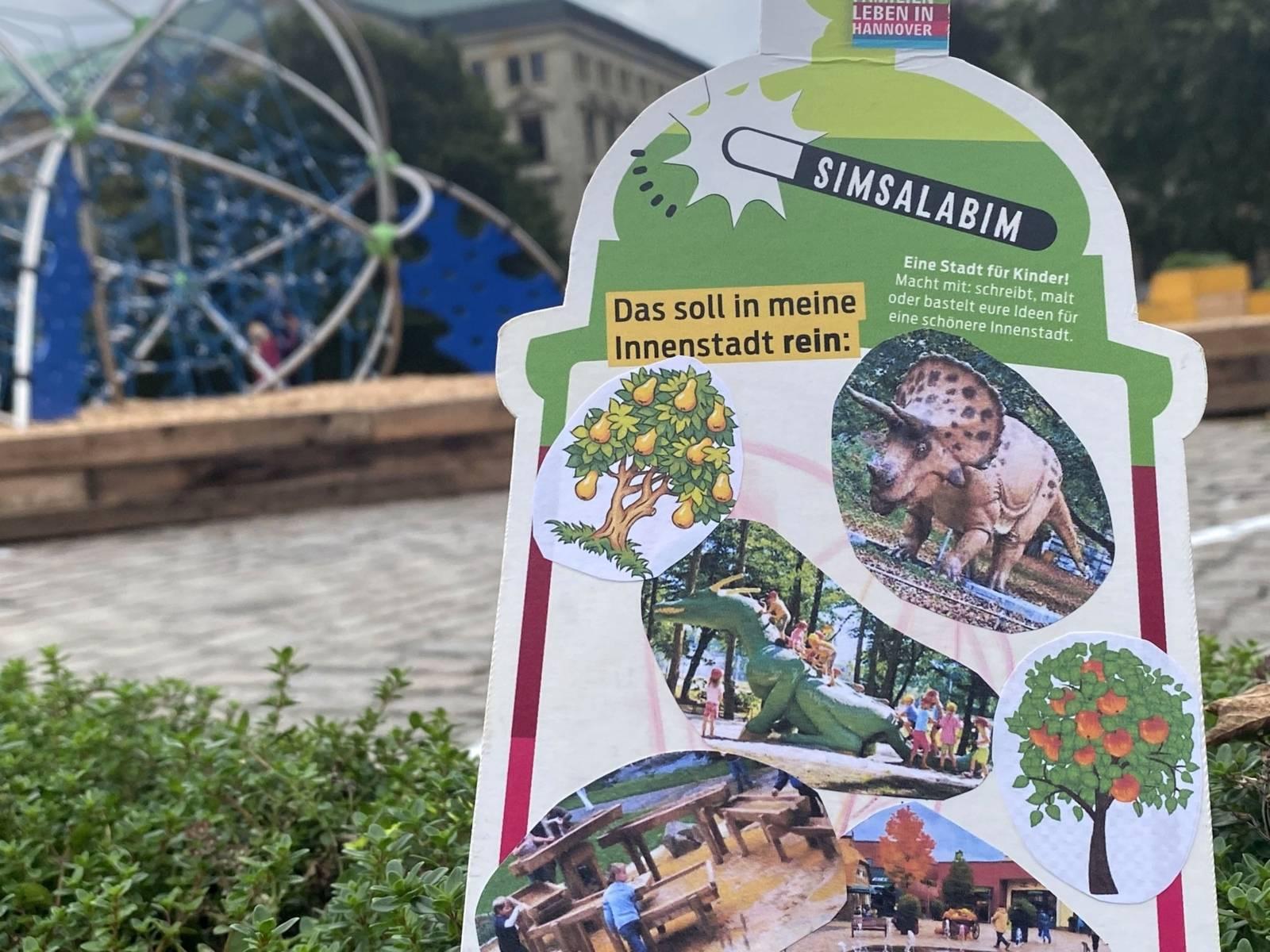 Im Hintergrund ein großes Klettergerüst in Unschärfe. Rechts eine Malkarte Simsalabim das soll rein Spielgeräte in Saurierformat
