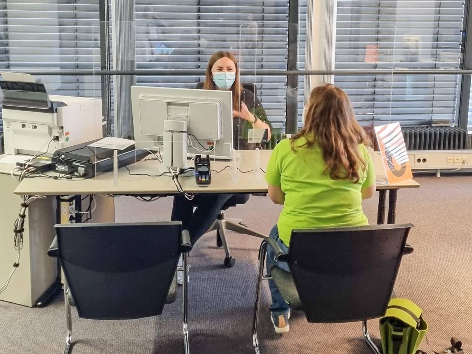 Zwei Personen sitzen sich an einem Schreibtisch gegenüber.
