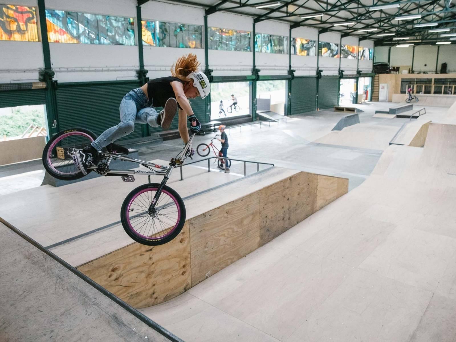 Eine Person auf einem Rad in einer Halle auf einer Rampe.