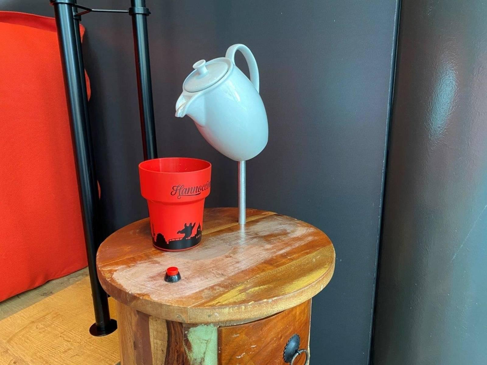 Der rote Hannoccino-Becher steht auf einen kleinen Schränkchen. Darüber ist eine blaue Kaffeekanne aus Porzellan installiert, die geneigt das Eingießen andeutet.