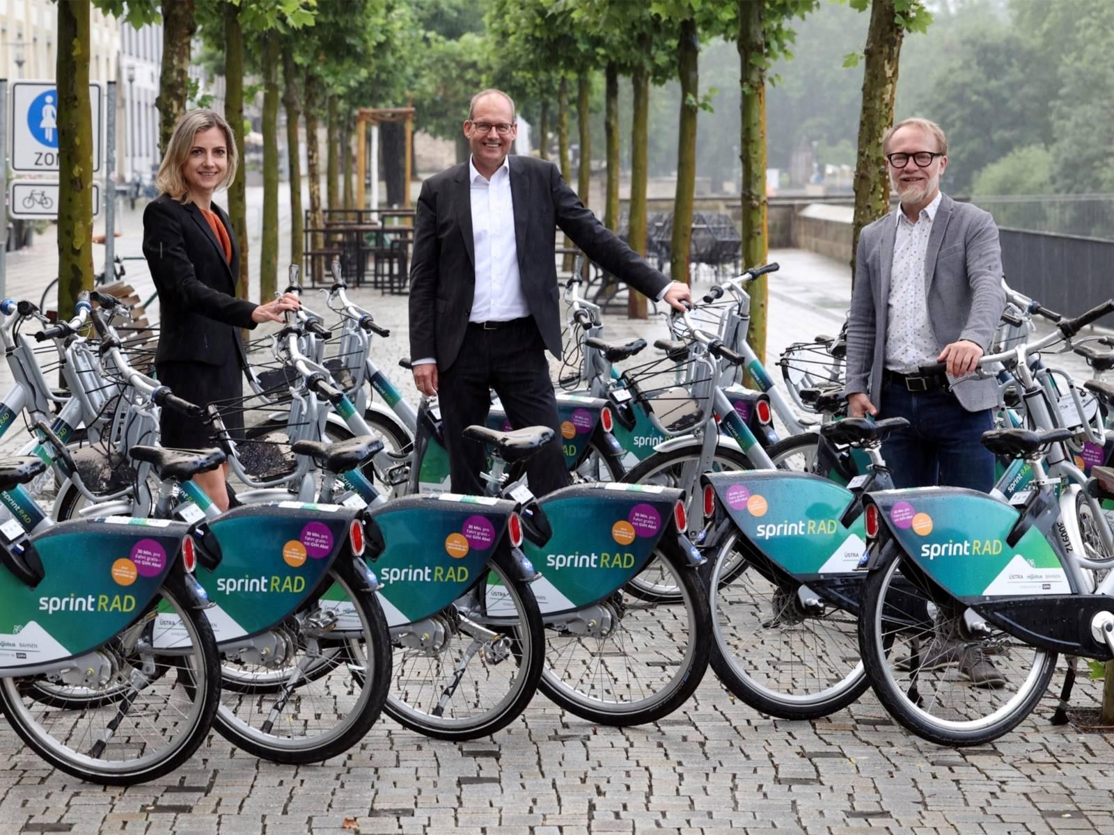 Zwei Männer und eine Frau präsentieren die neuen Mietfahrräder namens sprintRAD