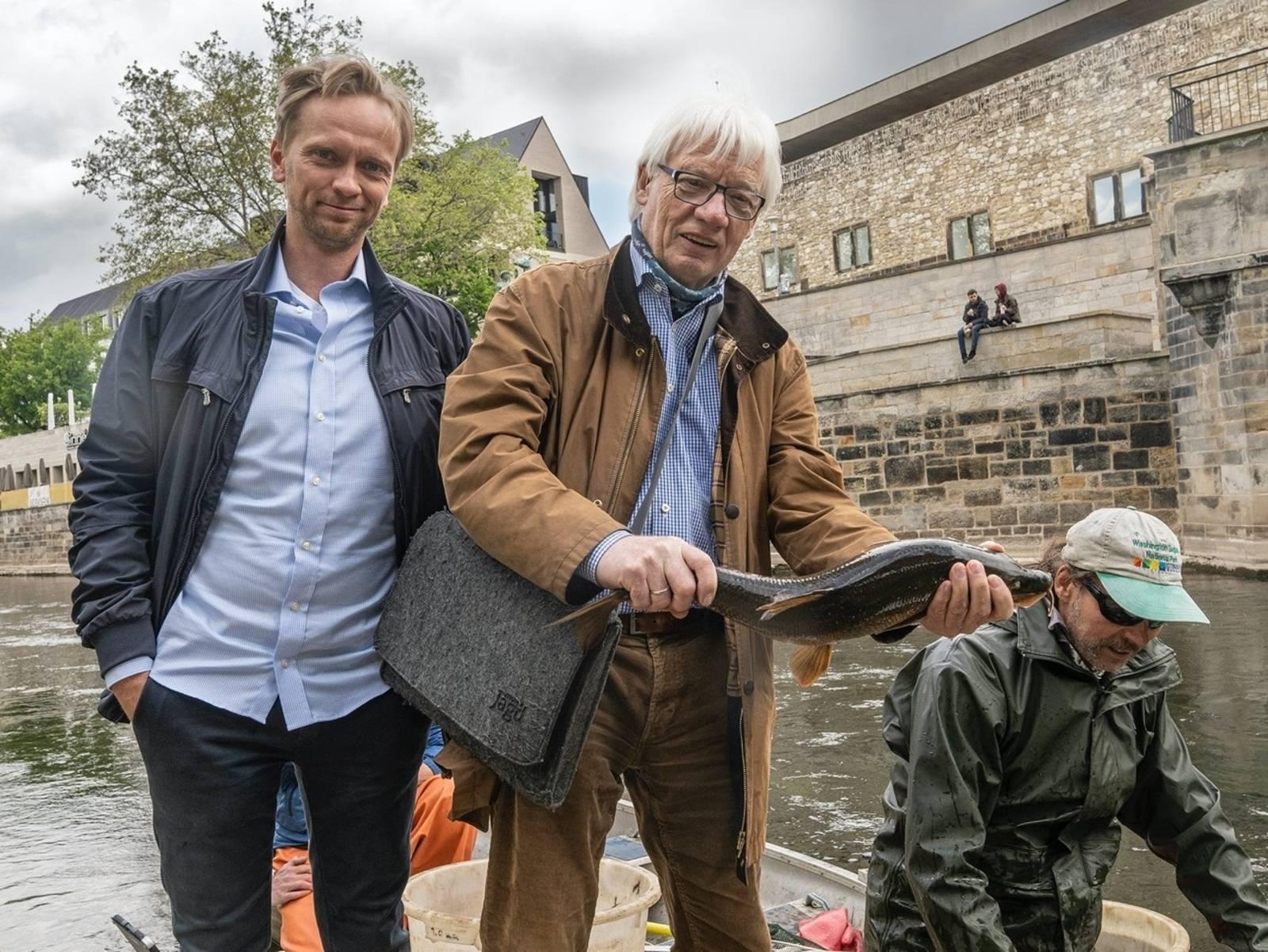Zwei Männer an einem Fluß, einer hält einen Fisch in den Händen