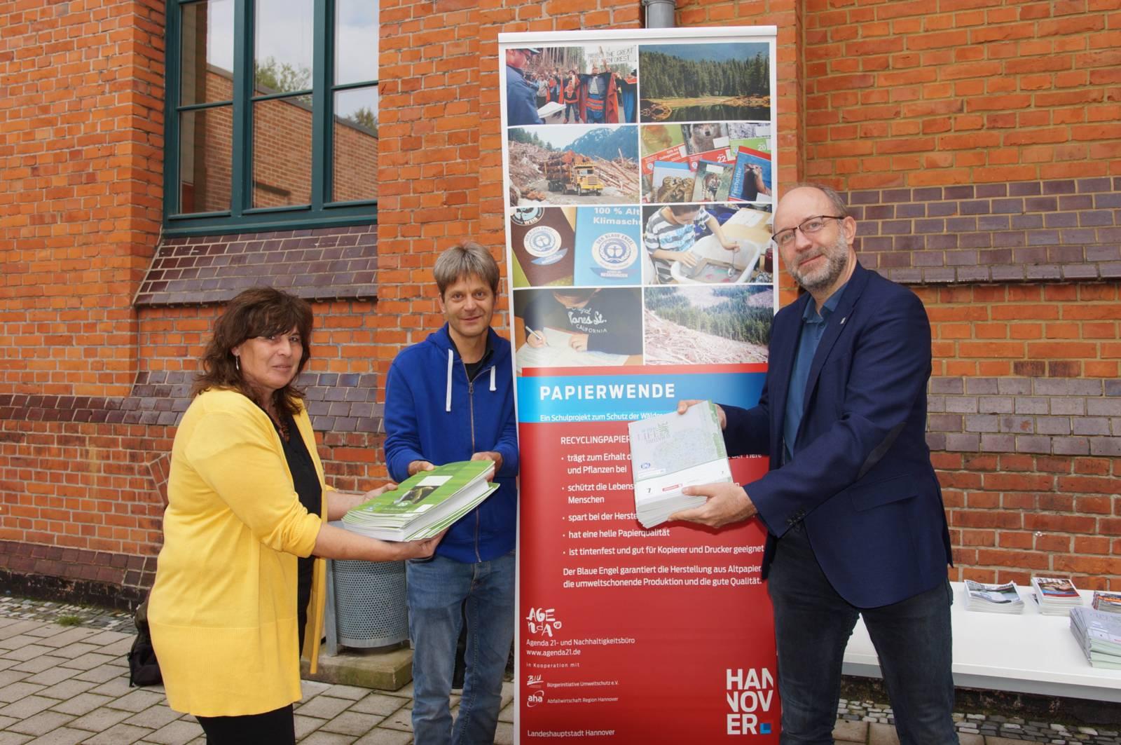 Drei Personen mit Recyclingpapier auf einem Schulhof.