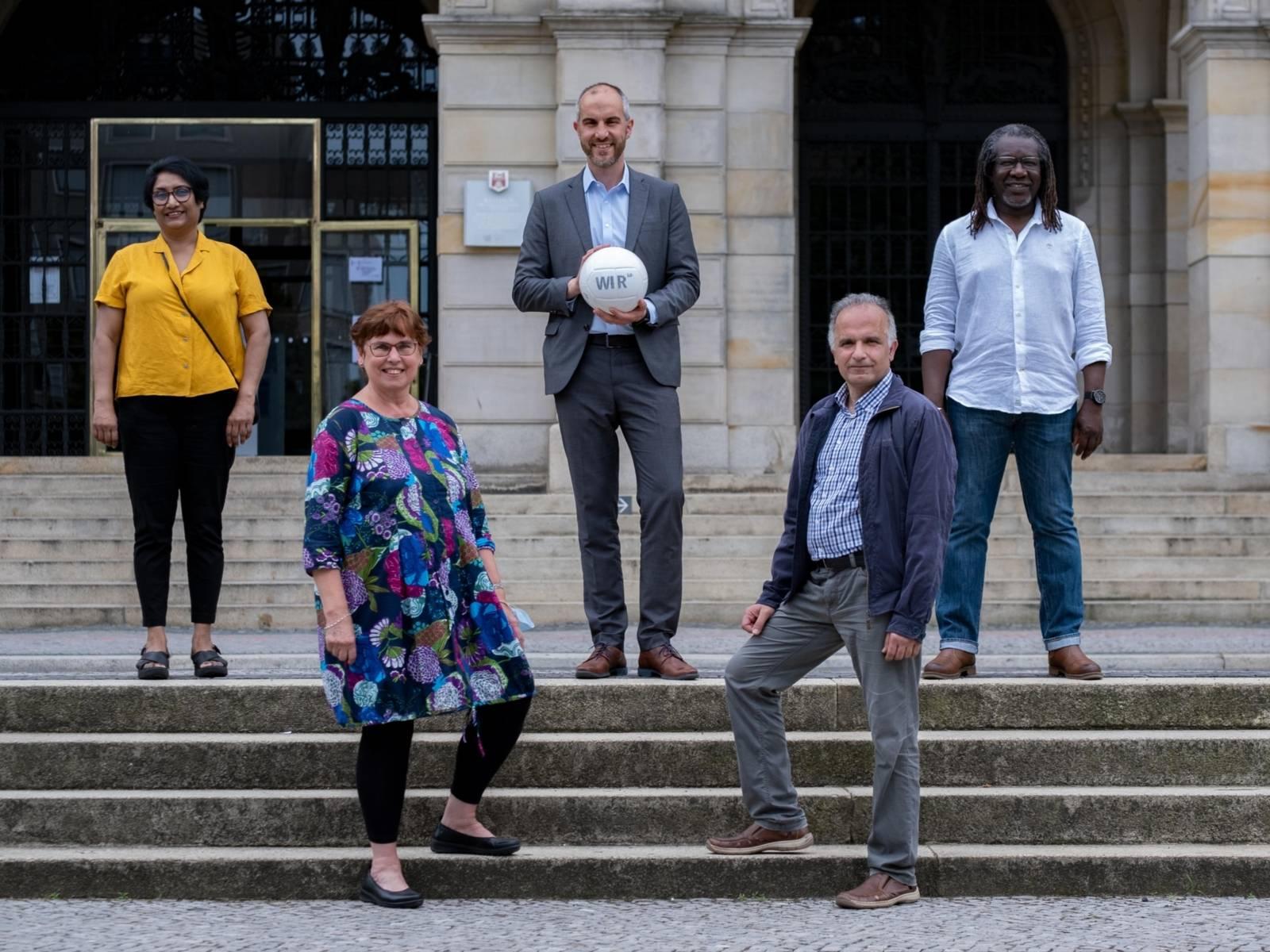 Fünf Personen mit einem Ball auf der Treppe vorm Neuen Rathaus.