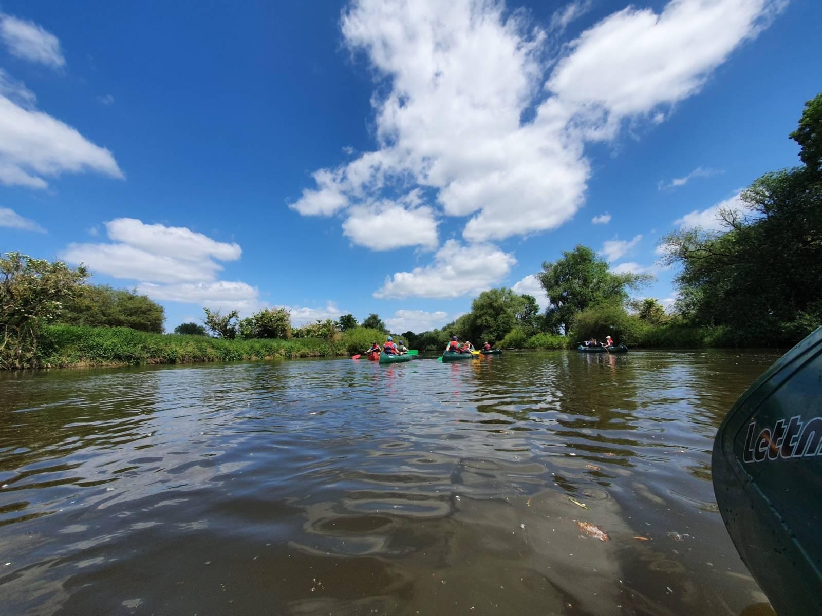 Blick nach vorn aus der Mitte des Flusses: In der Entfernung sechs bunte Paddelboote, rechts und links die grünbewachsenen Ufer, ein blauer Himmel mit Zirruswolken
