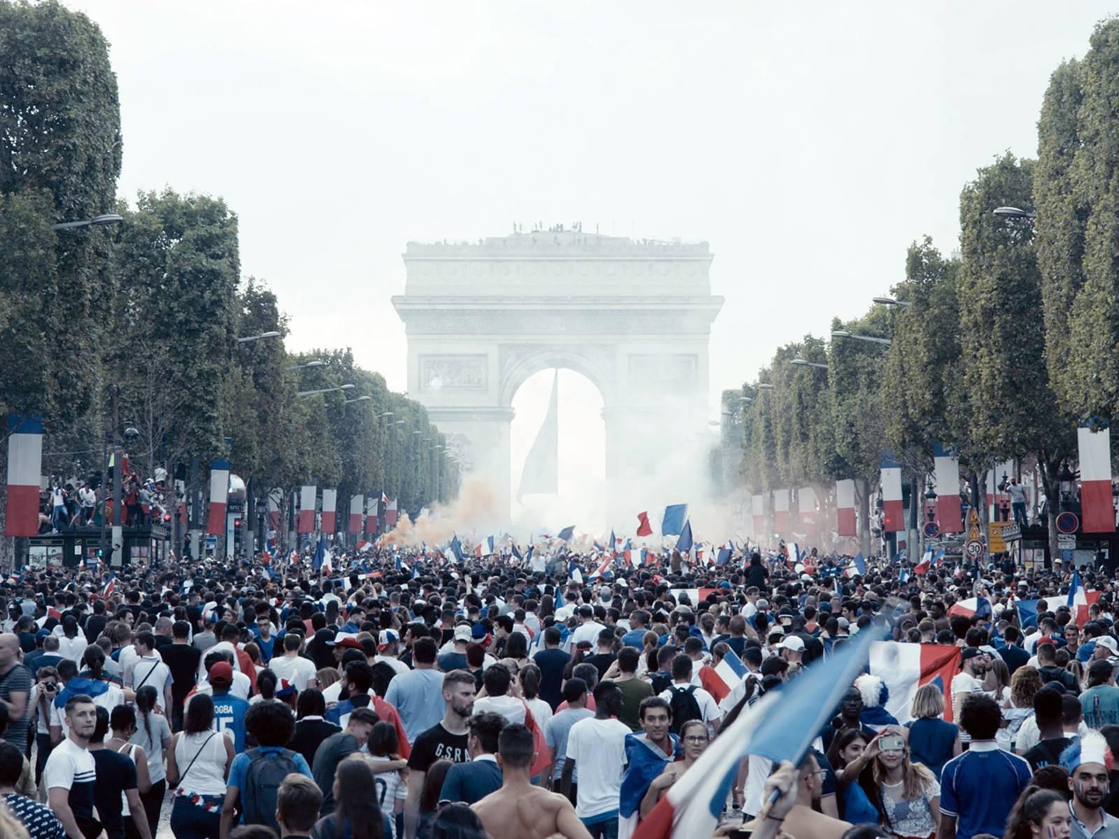 Auf dem Foto sind Menschenmassen vor dem Arc de Triomphe in Paris zu sehen. Rechts und links Baumreihen und viele französische Fahnen.