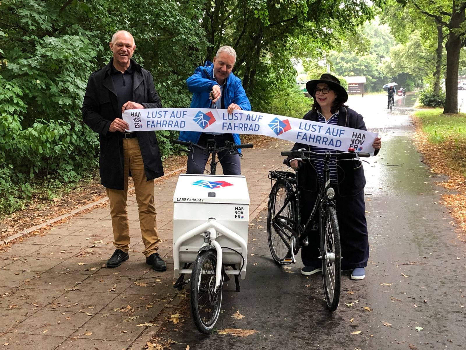 """Drei Personen stehen mit Fahrrädern auf einem Geh- und Radweg, ein Mann in der Mitte schneidet ein Band mit der Aufschrift """"Lust auf Fahrrad"""" durch."""