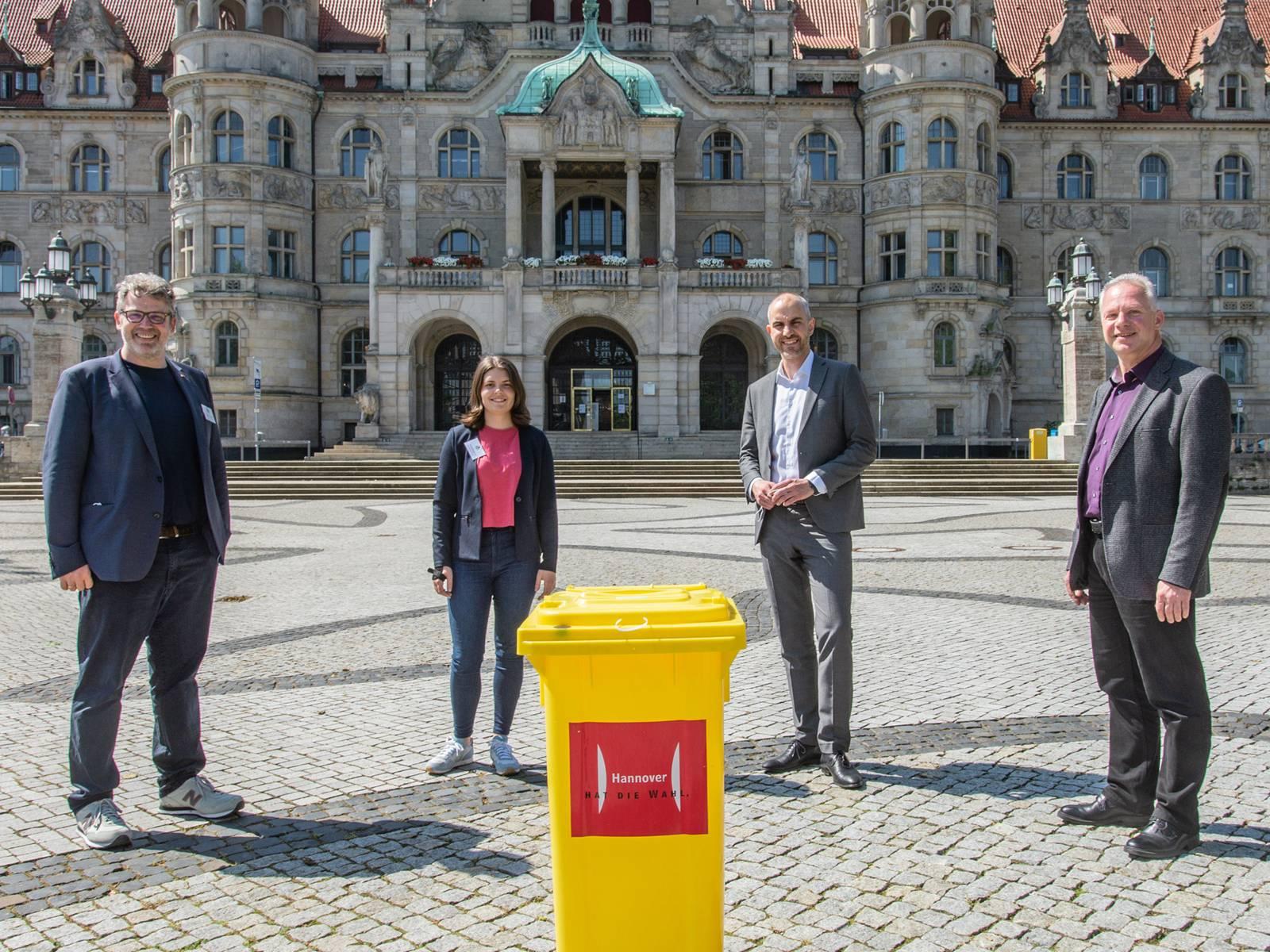Vier Personen stehen um eine gelbe Wahlurne herum auf dem Trammplatz vor dem Neuen Rathaus