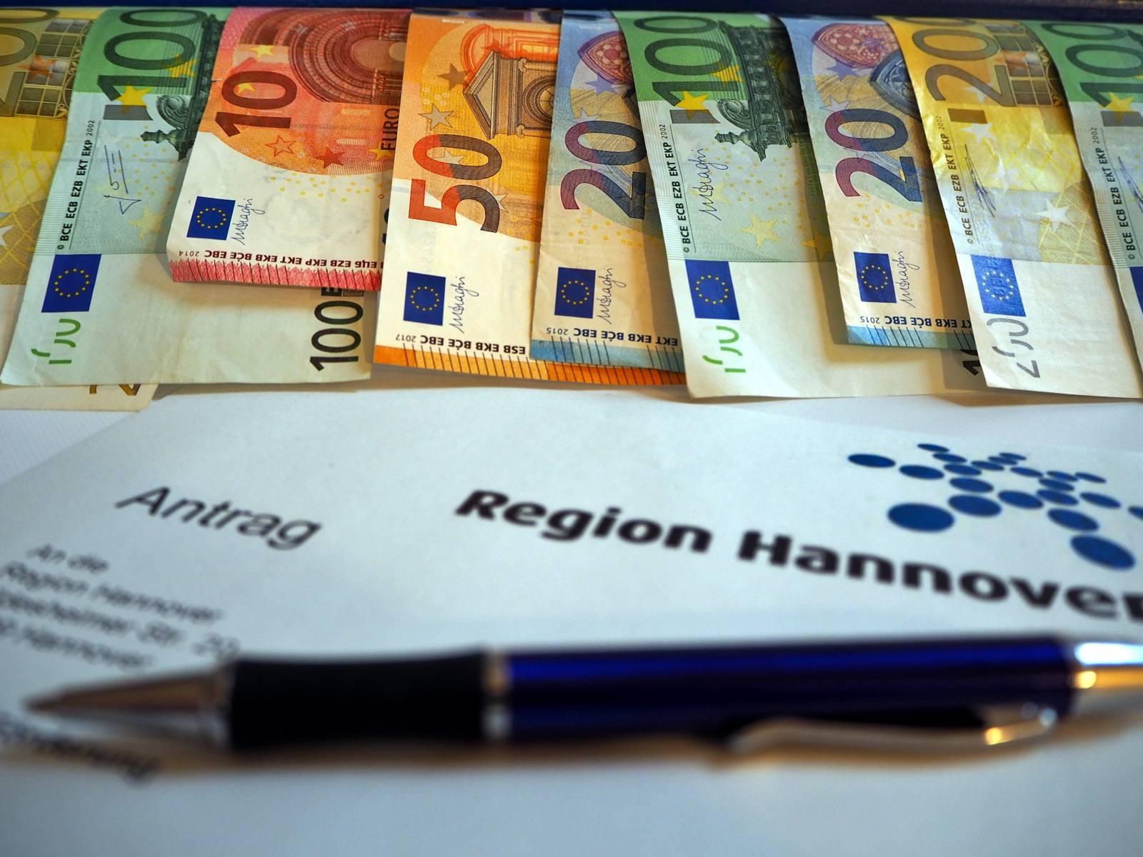 """Geldscheine hängen von einem blauen Holzstück, auf dem """"Region Hannover"""" steht."""