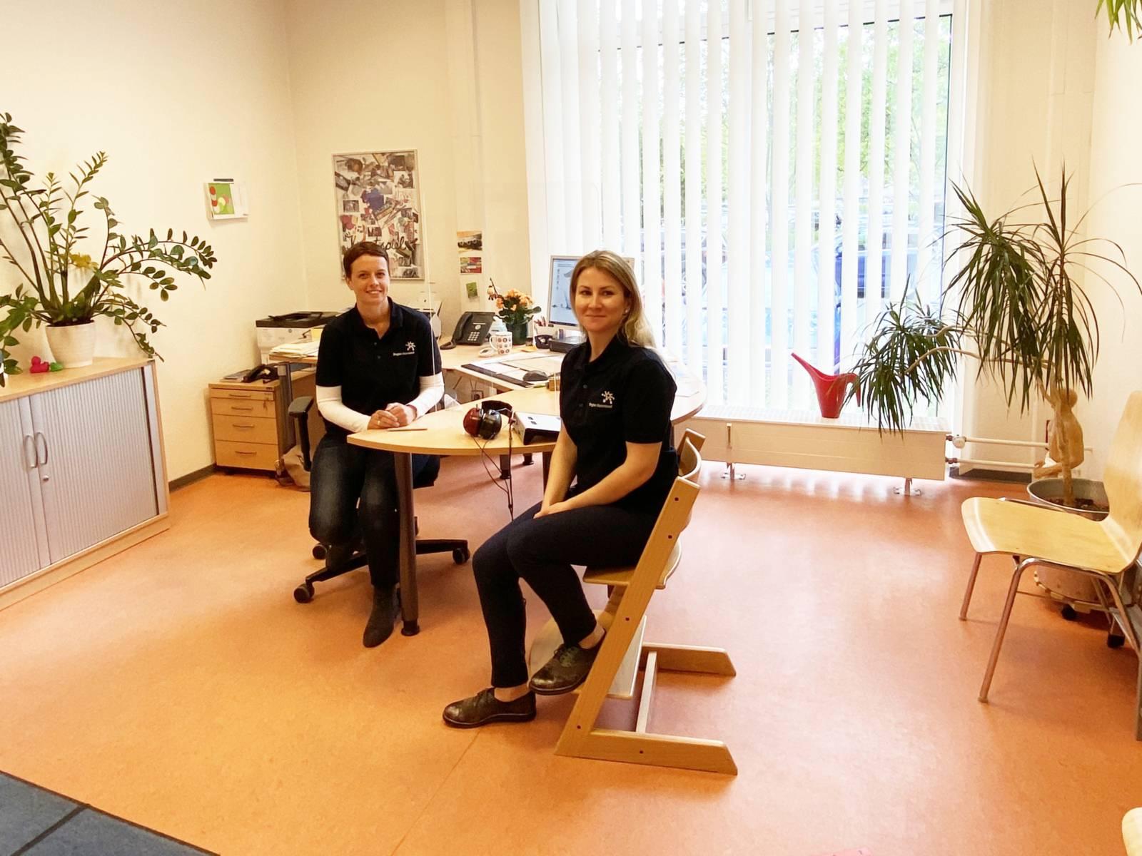 Zwei Frauen, die an einem Schreibtisch mit Besprechungstisch sitzen
