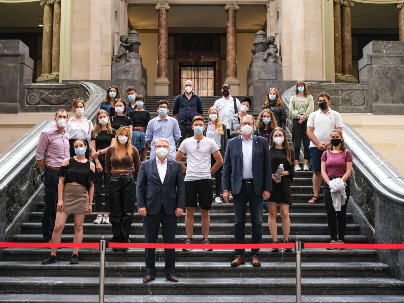Gruppe von rund 20 Personen auf einer Treppe in einer Halle. Alle tragen einen Mund-Nasen-Schutz.