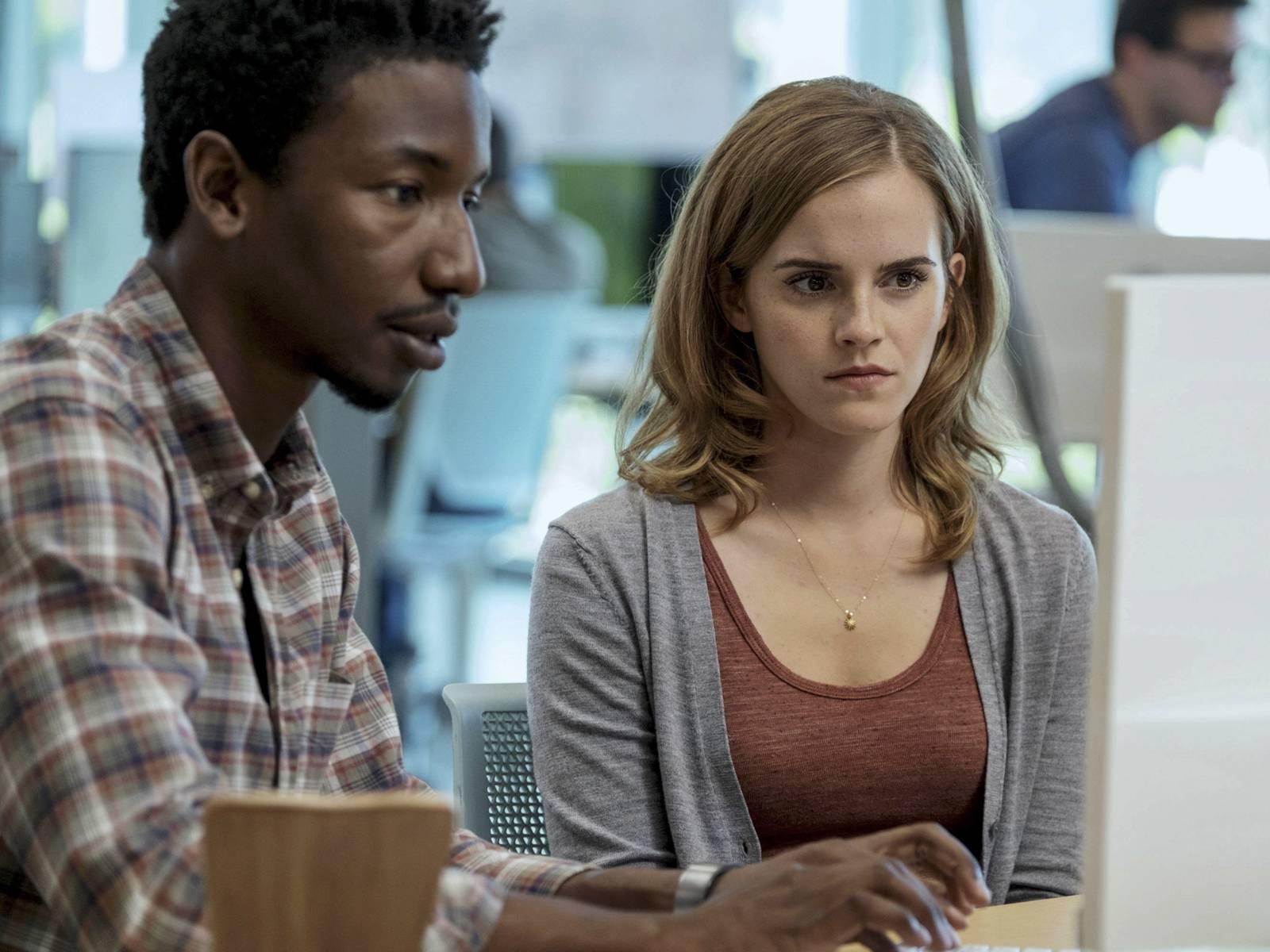 Ty, ein schwarzer junger Mann, und Mae Holland, eine weiße junge Frau sitzen nebeneinander vor einem Computerbildschirm.