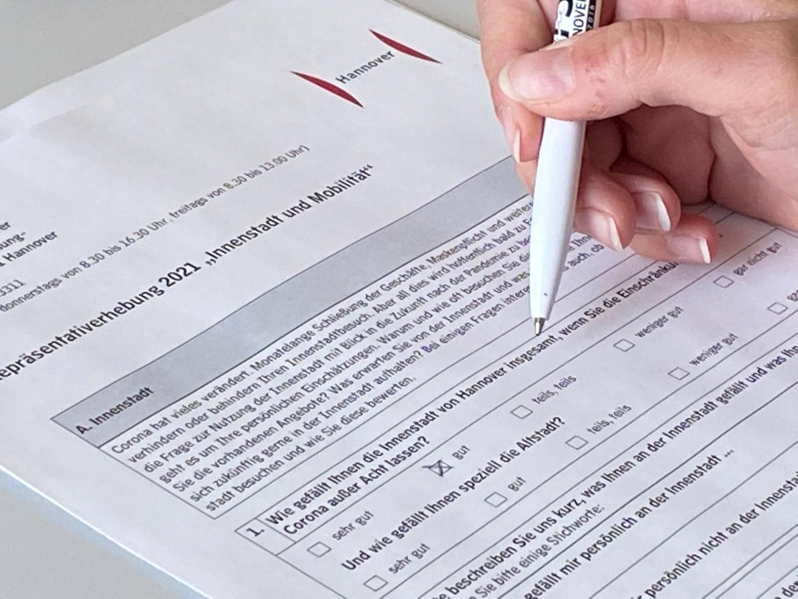 Eine Hand, die einen Fragebogen ausfüllt.