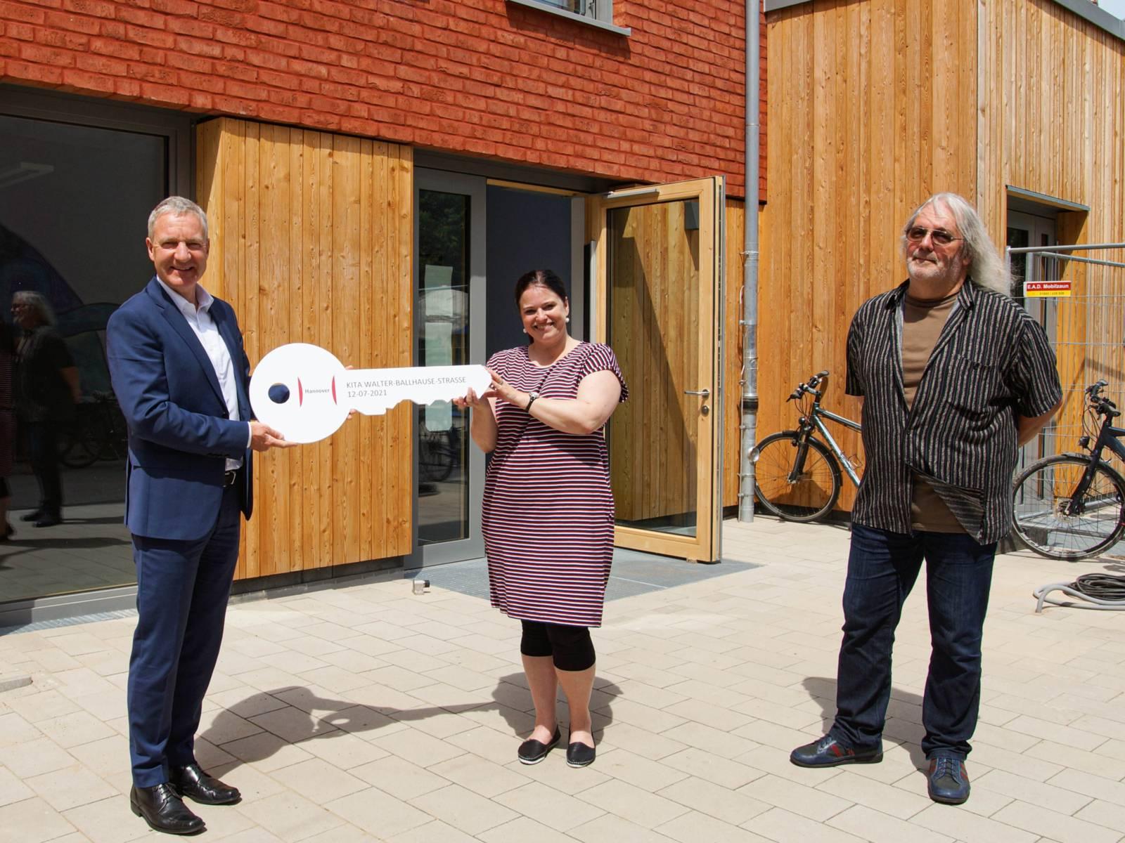 Drei Personen mit einem gro´ßen Schlüssel vor einem Gebäude.