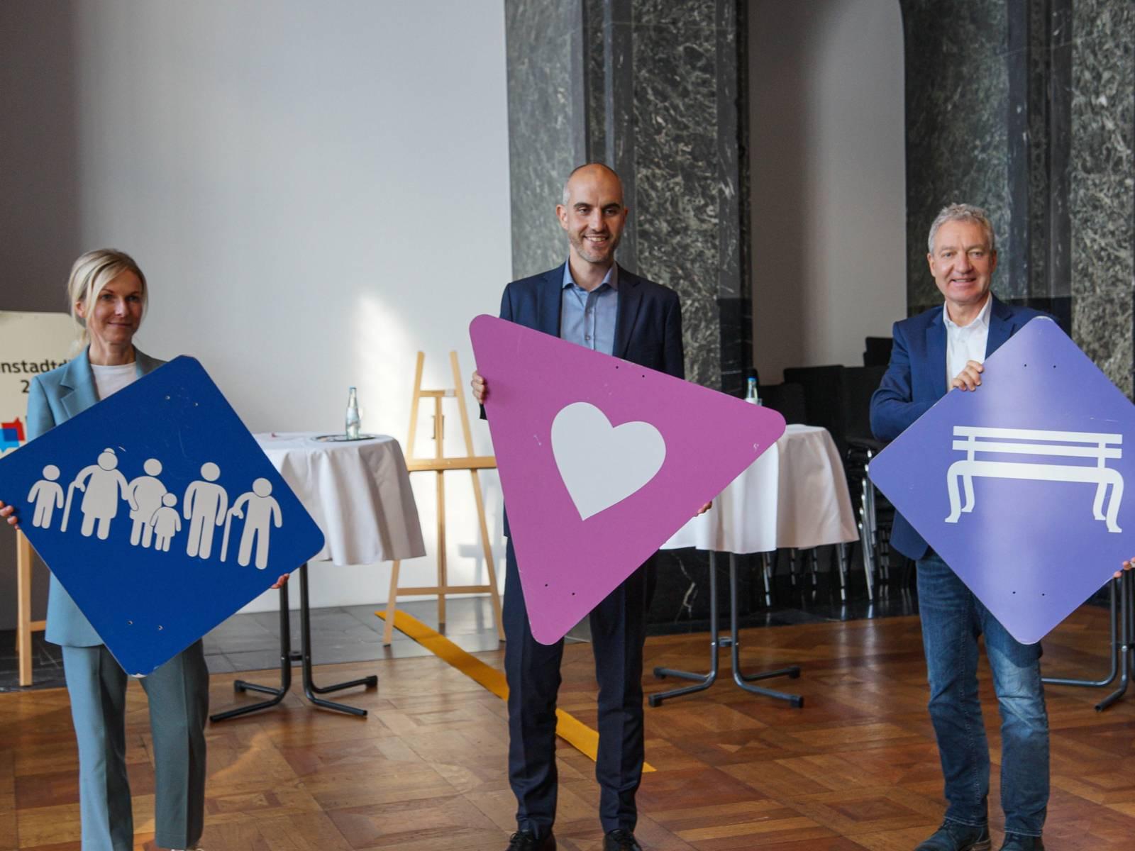 Drei Personen mit Schildern in einem Saal.