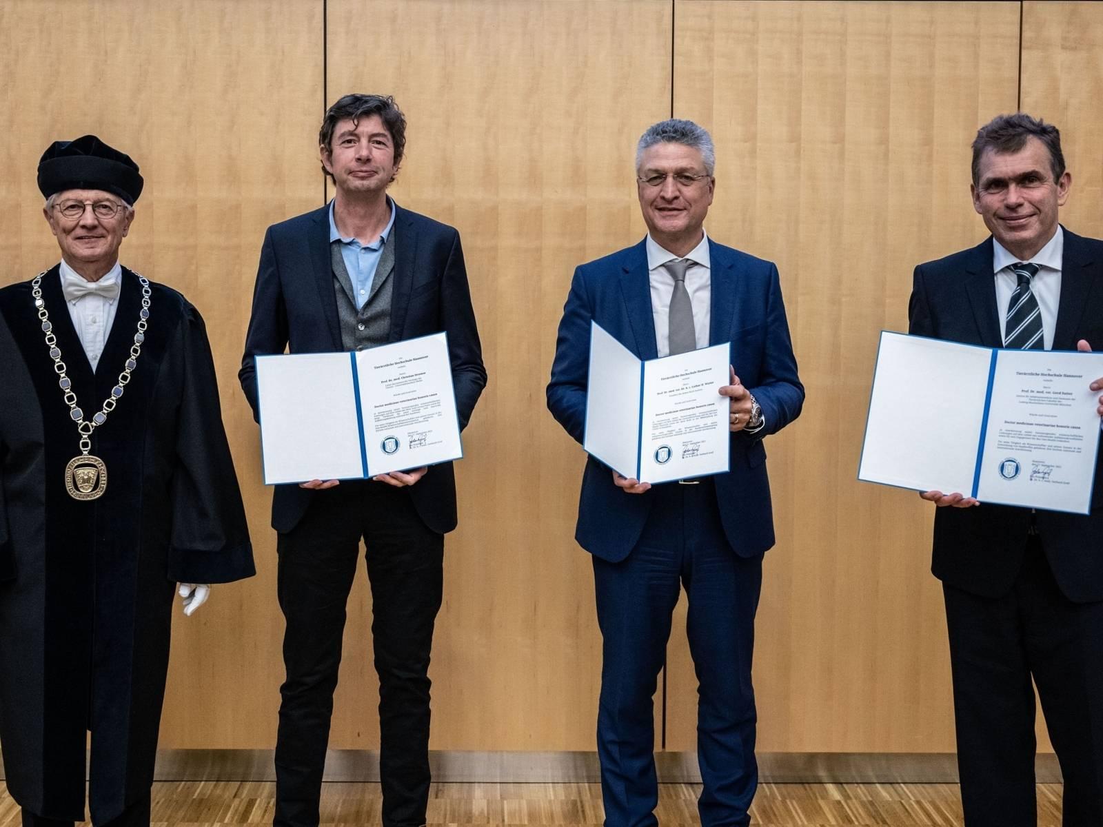 Vier Männer, einer in Amtstracht mit Amtskette, drei halten Urkunden in die Kamera.