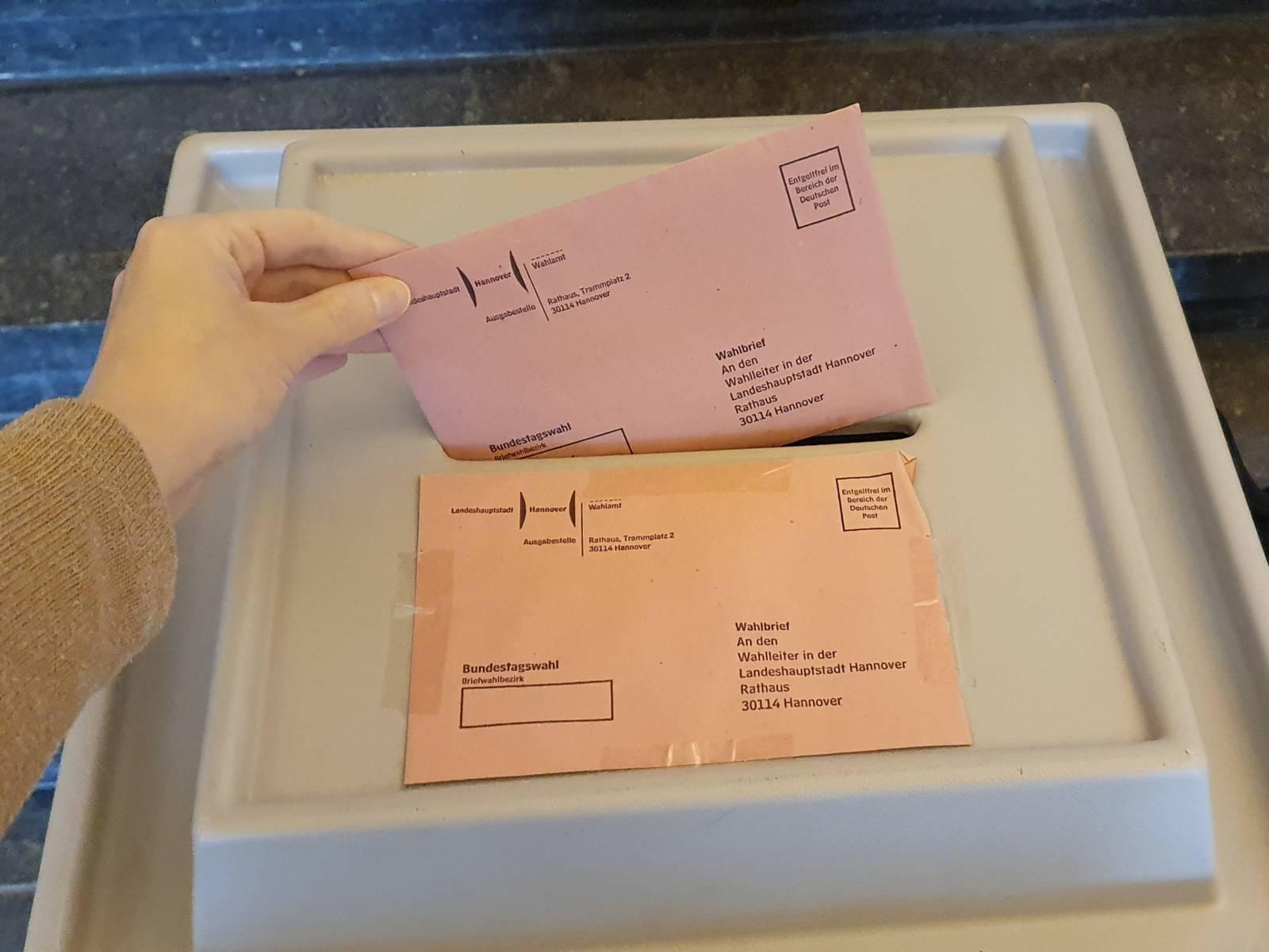 Ausschnitt einer Hand, die einen Wahlbrief in eine Wahlurne wirft