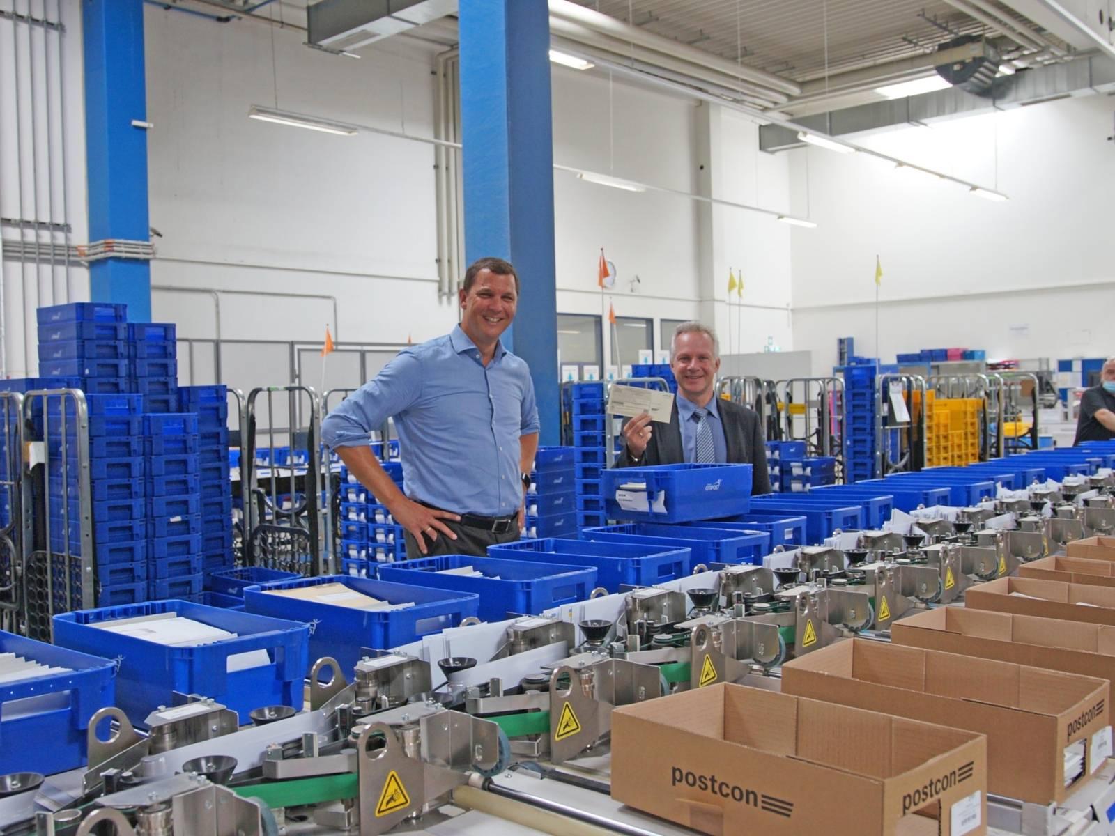 Zwei Männer vor eine Menge Behältnissen mit Wahlzetteln.