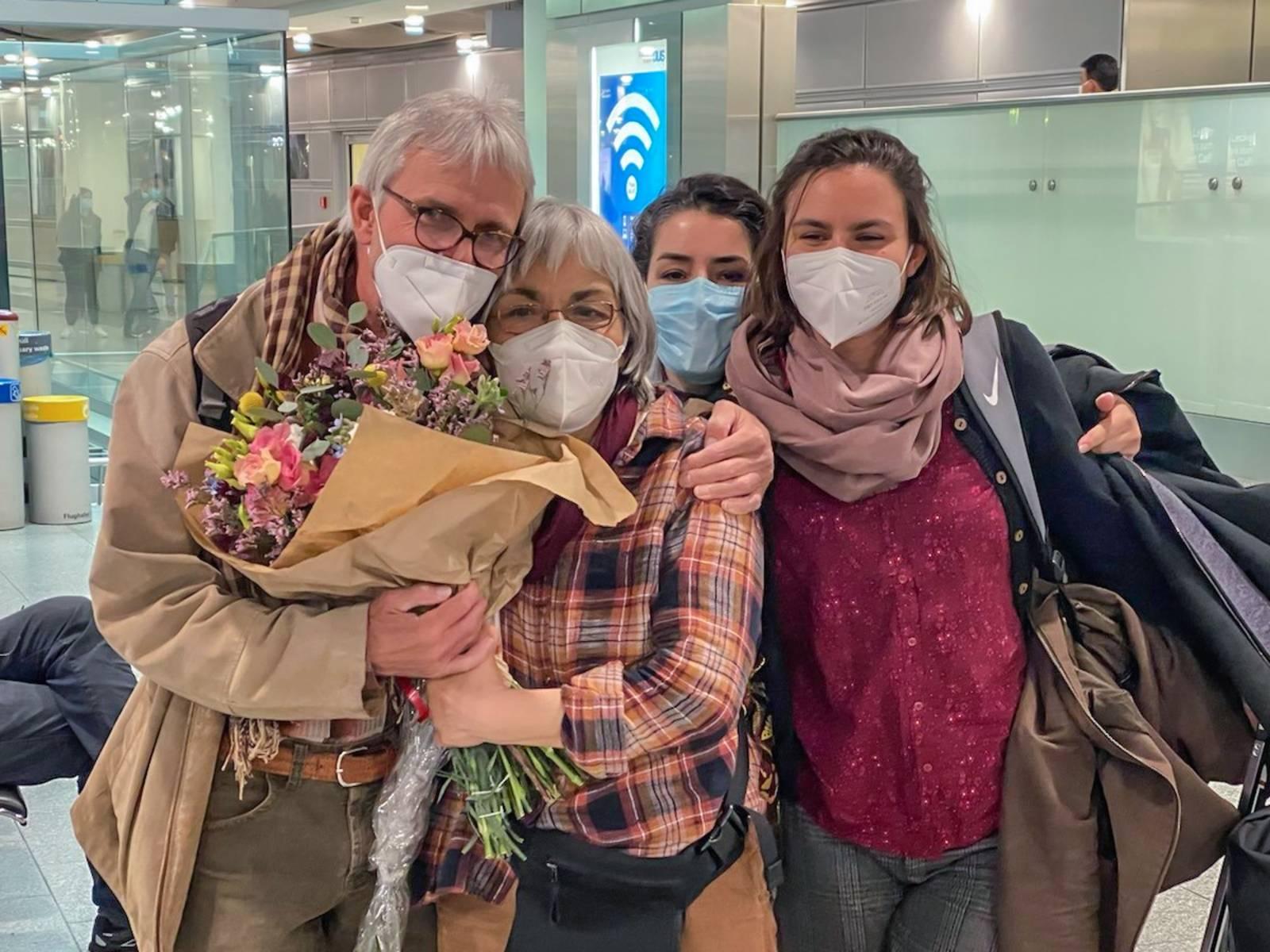 Drei Frauen und ein Mann, die eng beieinander stehen; eine der Frau hält einen Blumenstrauß in der Hand, alle tragen FFP2-Masken