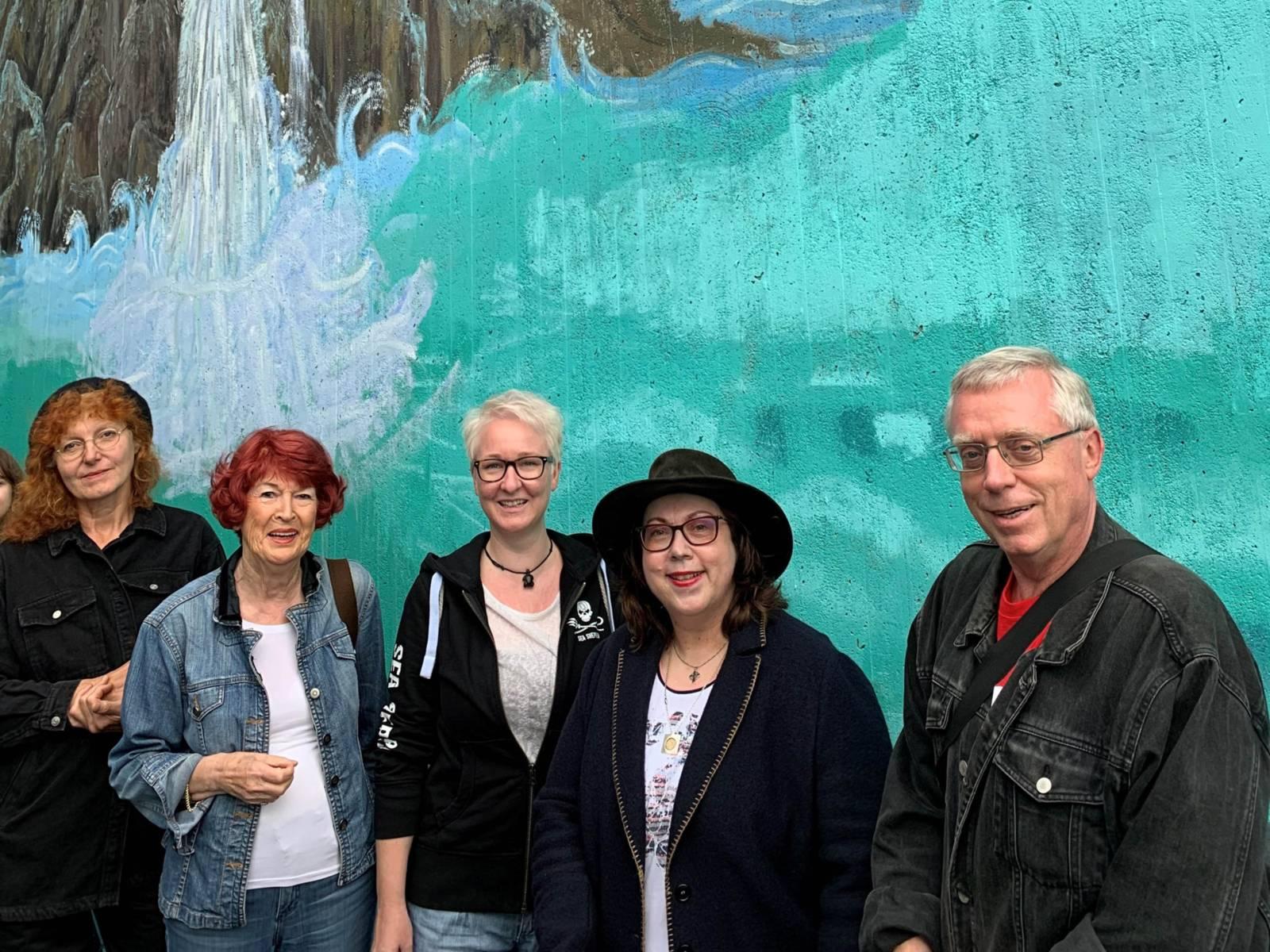 Fünf Personen vor einem Wandbild.