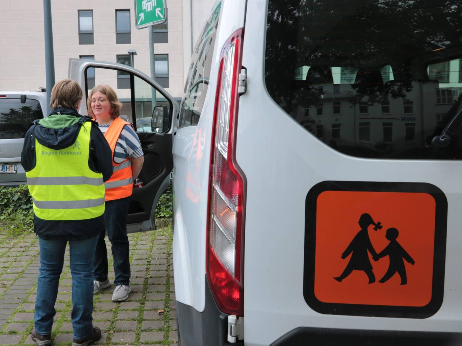 Zwei Personen stehen neben einem weißen Bus zur Schülerbeförderung.