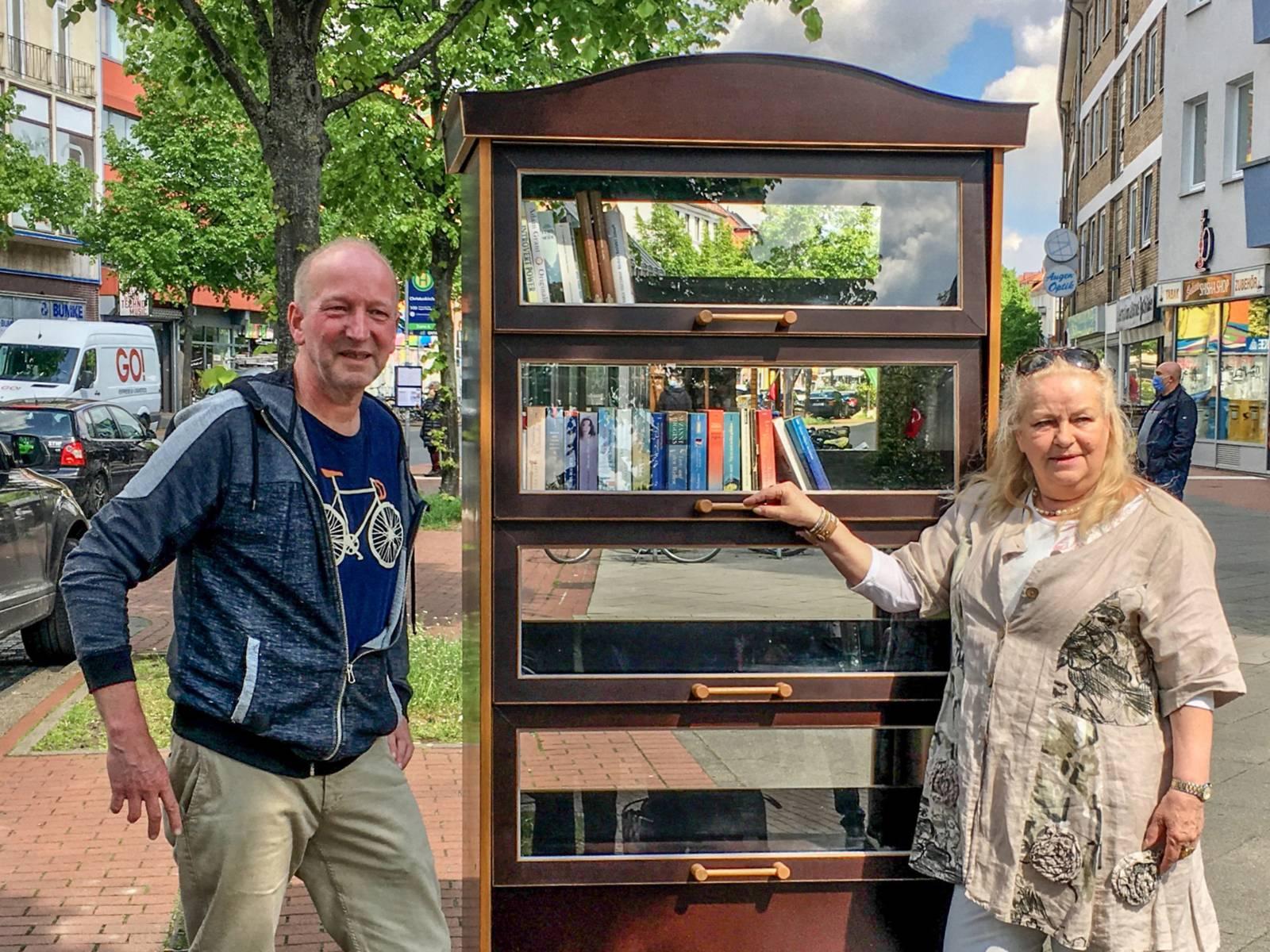 Zwei Personen stehen an einem Bücherschrank